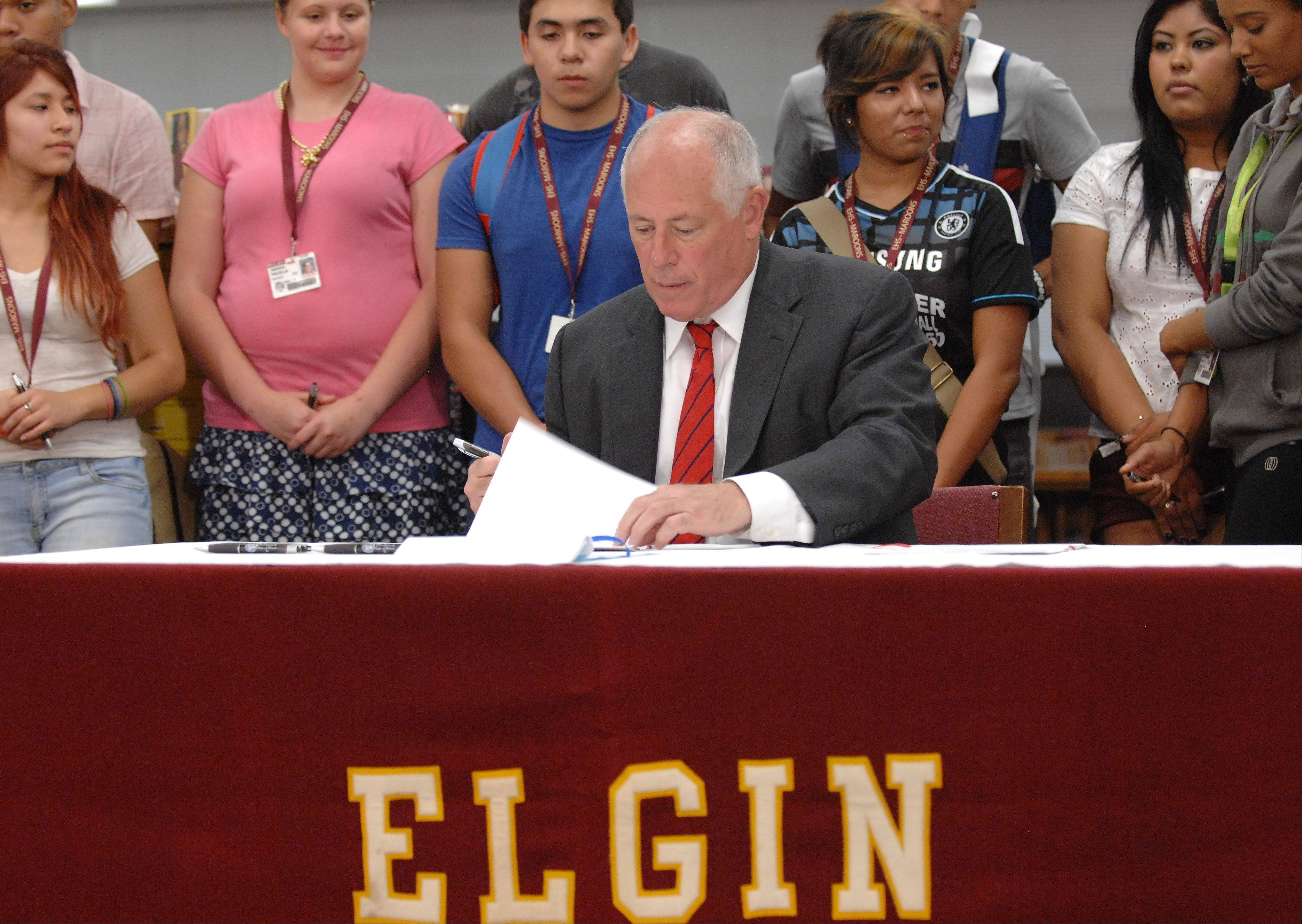 Gov. Pat Quinn signs a bill at Elgin High School Monday that will allow the police to share information with schools if there is an investigation of a student. The bill is in response to the attack on Elgin High School teacher Carolyn Gilbert.
