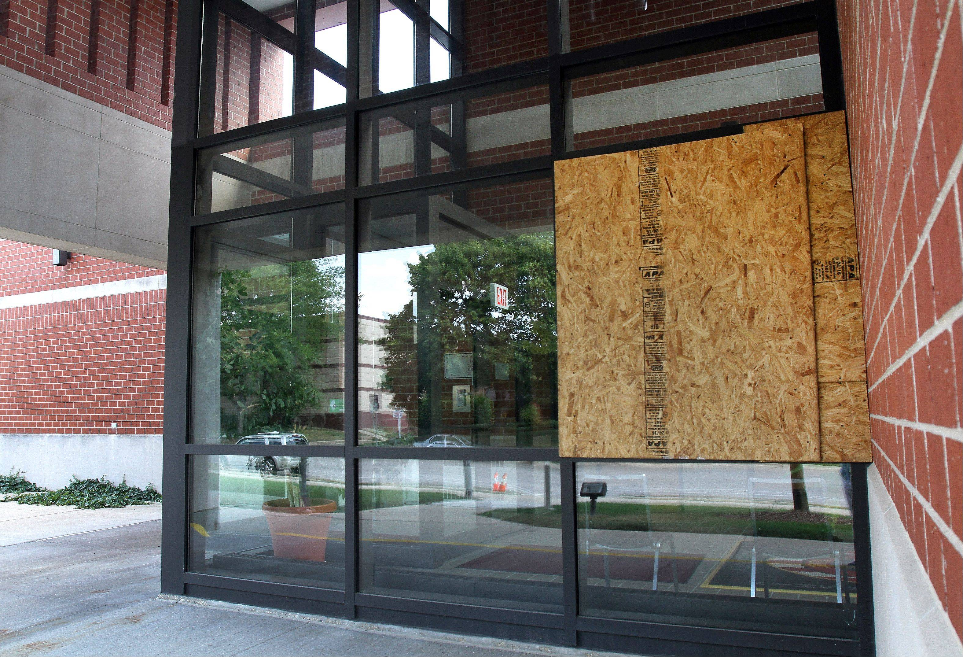 Wheaton police boarded up a lobby window after Robert Davison threw a brick through it in July. He has been sentenced to a year in prison.