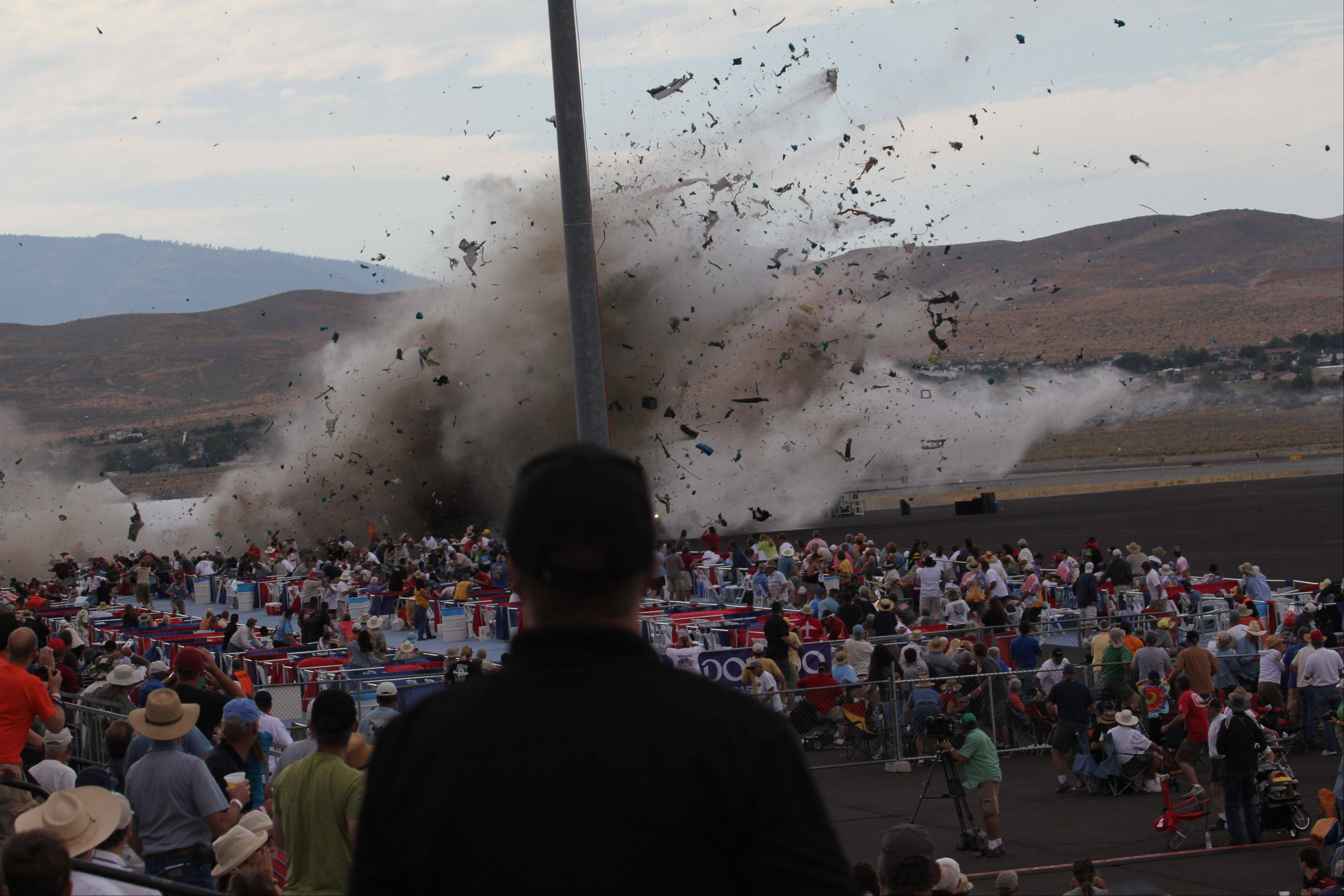 In this Sept. 16, 2011 file photo, A P-51 Mustang airplane crashes into the edge of the grandstands at the Reno Air show in Reno, Nev, leaving 11 people dead and 70 seriously injured. The National Transportation Safety Board, meeting in Washington, will determine the cause of the September 2011 crash of a modified World War II-era fighter plane into a spectator area during the 2011 National Championship Air Races in Reno on Monday, Aug. 27, 2012.