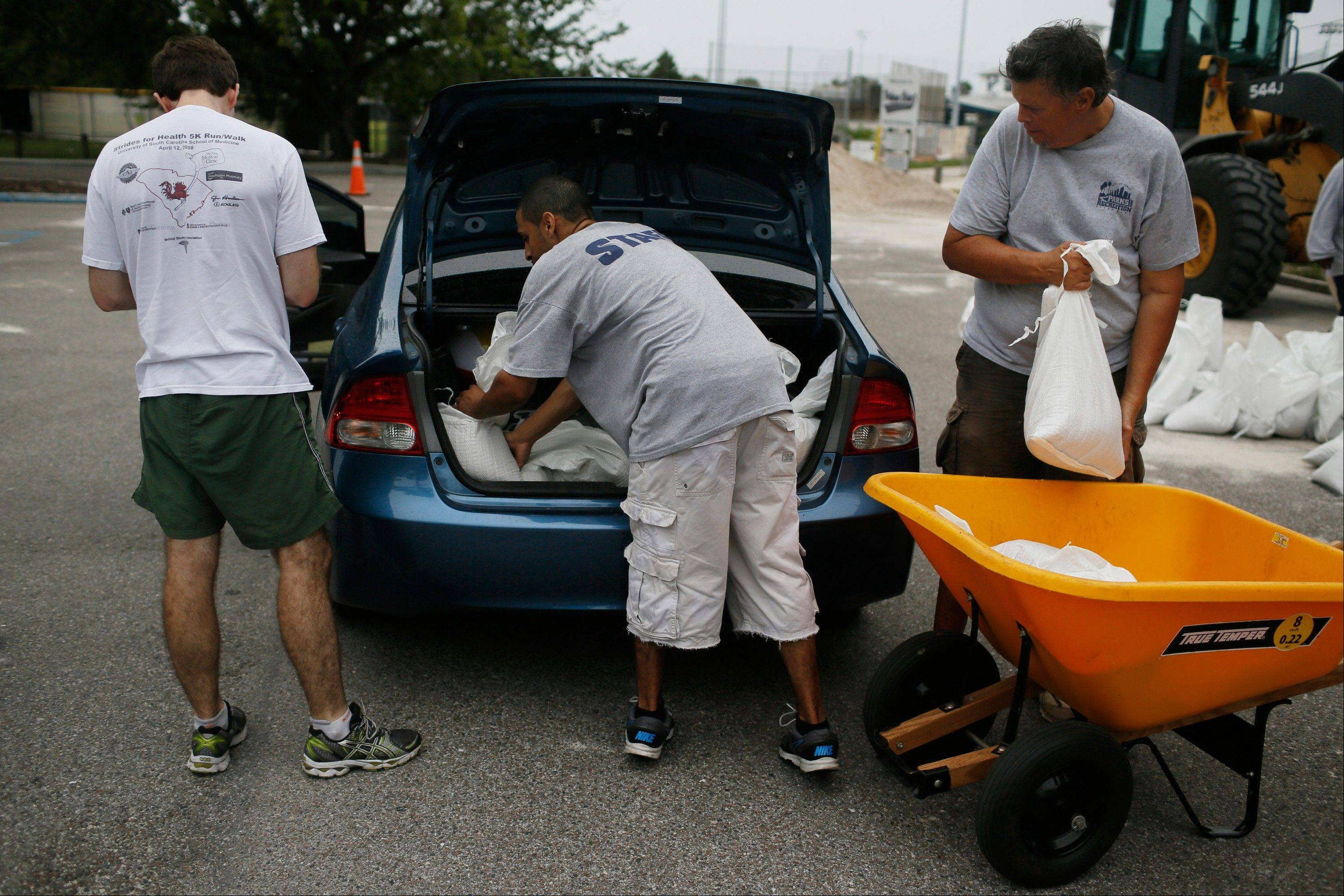 City of Tampa workers put sand bags in the boot of a vehicle in Tampa, Fla., on Sunday, Aug. 26. Tropical Storm Isaac regained strength as it entered the Gulf of Mexico, forcing oil and gas production sites in its path to close and threatening the coasts of four U.S. states with a possible Category-2 hurricane.