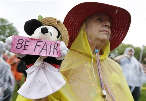 Demonstrator Carole Fields, of Palm Beach, Fla., listens to a speech, Monday, Aug. 27, 2012, in Tampa. Hundreds of protestors gathered in a park in Tampa to march in demonstration against the Republican National Convention.