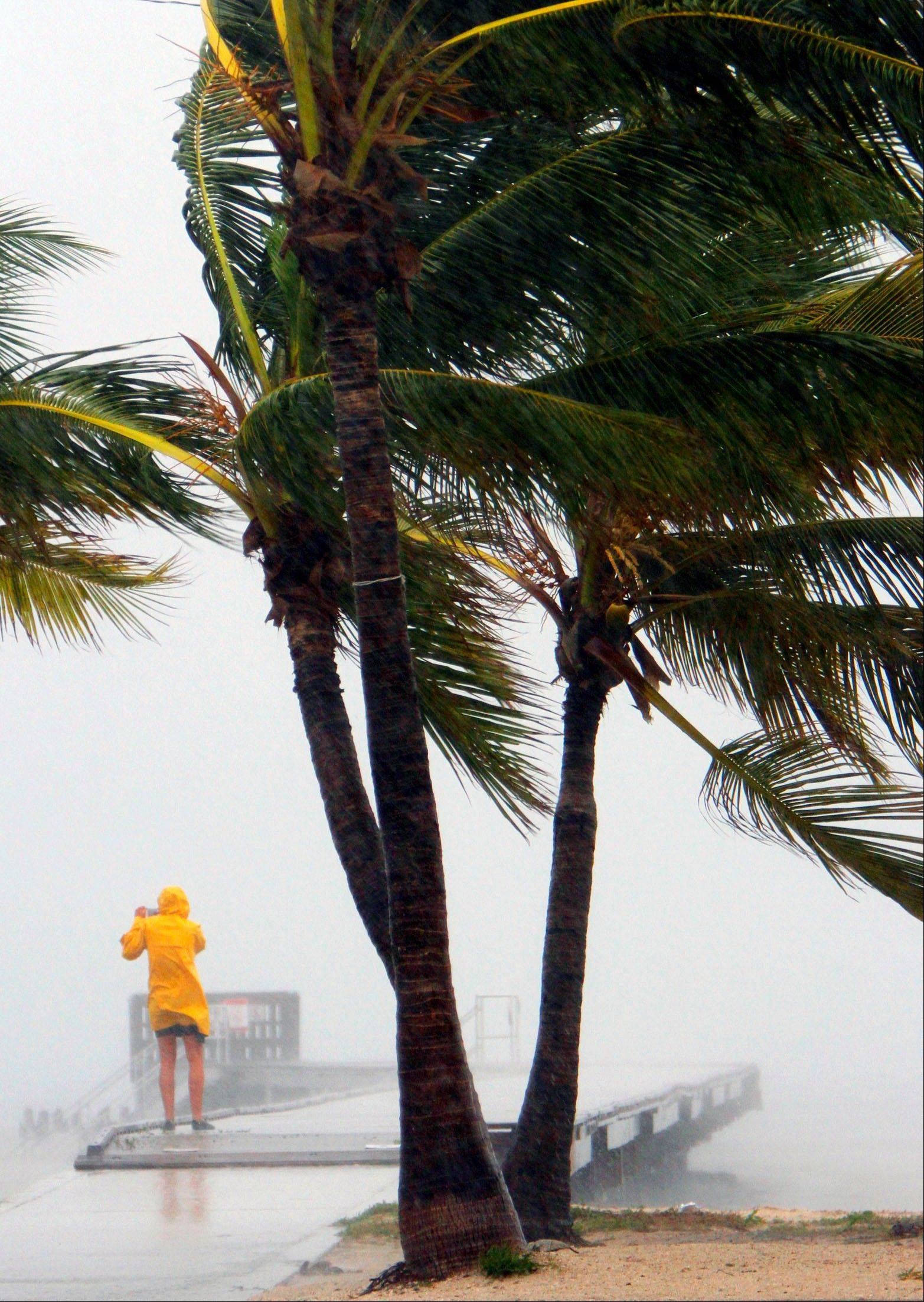 A person braves the rain at Clarence Higgs Beach in Key West, Fla., as Tropical Storm Isaac hits the area on Sunday. Isaac gained fresh muscle Sunday as it bore down on the Florida Keys, with forecasters warning it could grow into a dangerous Category 2 hurricane as it nears the northern Gulf Coast. The Republican National Convention set to start Monday will be adjourned after it's called into session and all programming scrapped until Tuesday.