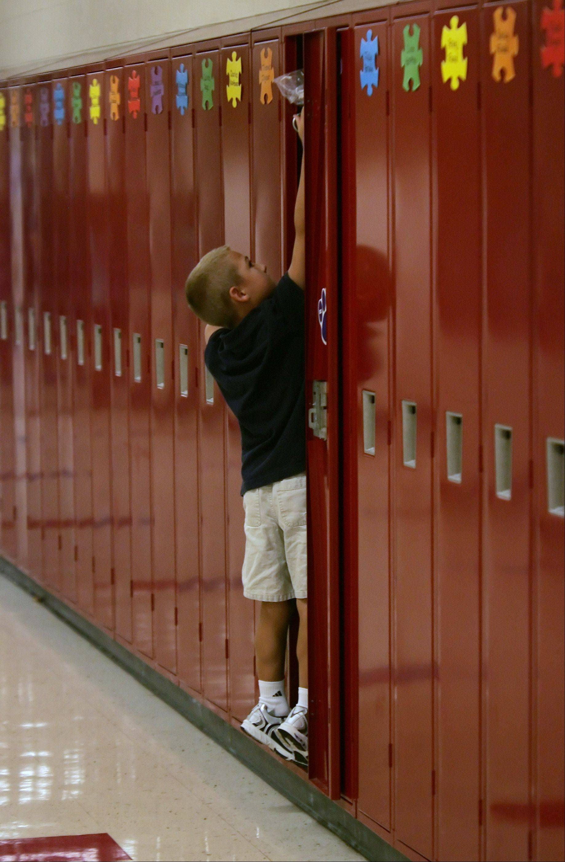 Fourth grader Ben Heft stands in his locker putting away his school supplies during the first day at Millburn Elementary School Thursday. This wing of the school last year held the middle school classes. This is the first year that the entire building is being used as only an elementary school instead of combined with a middle school.