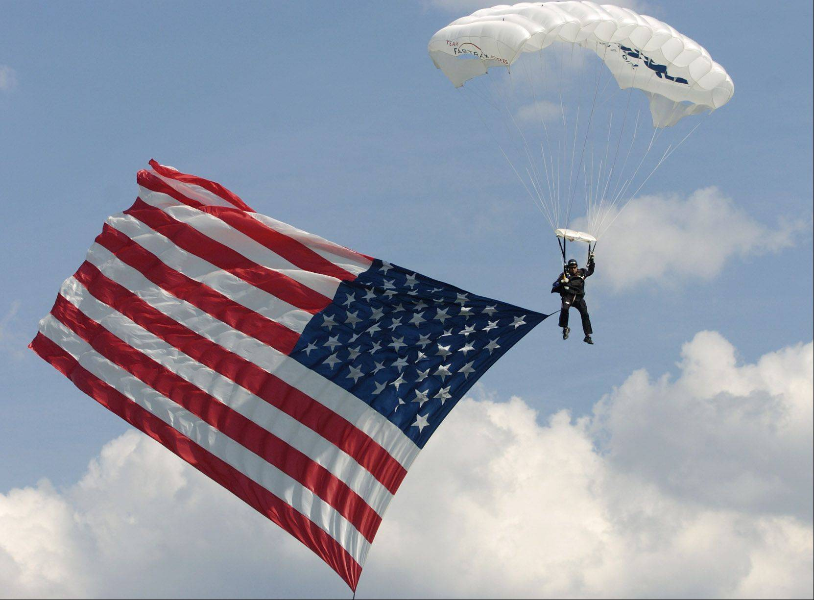 Former Army Ranger Dave Hart sky-dives with an 1100 square foot American flag during a ceremony at Newport Cove in Antioch, honoring Nick Mapson, Army veteran severely burned in a roadside bomb attack in Afghanistan.