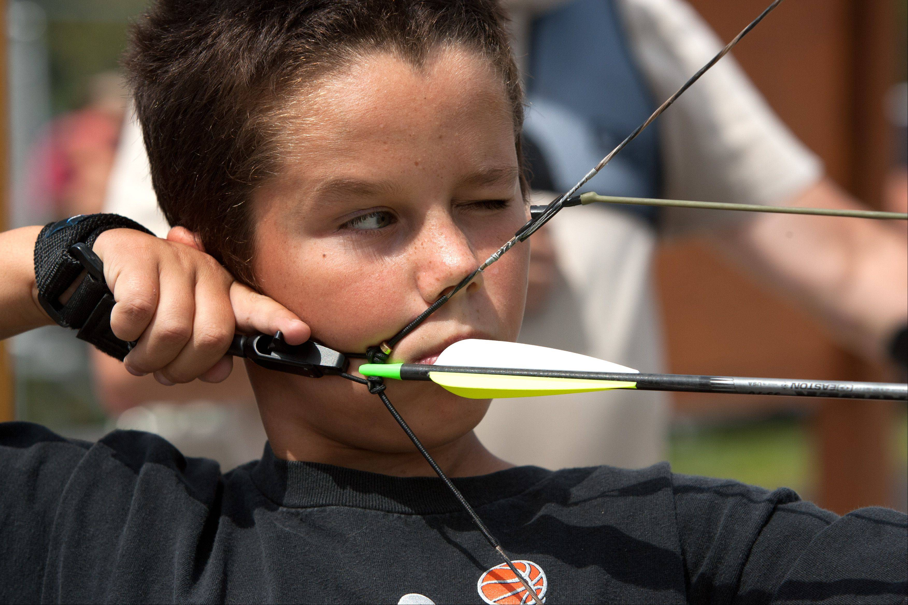 Ray Black, 11, of Wheaton eyes his target, during the DuPage County Forest Preserve's opening of an upgraded archery range, at the Blackwell Forest Preserve.