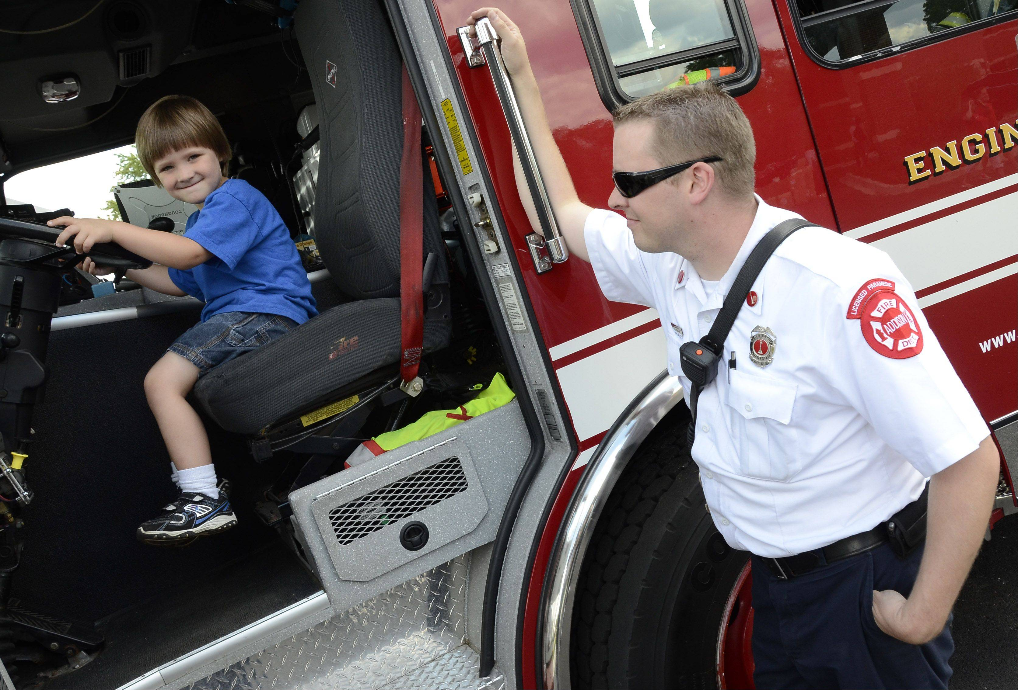 Christopher Kaul, 4, of Elmhurst gets to steer a fire truck Sunday at the opening of the Elmhurst Memorial Hospital Addison Health Center. Looking on is Addison Fire Department Lt. firefighter /paramedic Chris Mansfield.