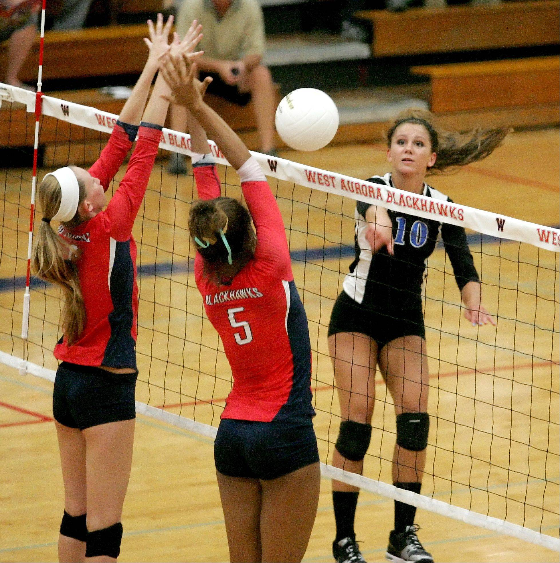 Hannah Buck of Geneva hits the ball past Nerissa Vogt of West Aurora in girls volleyball action in Aurora on Monday.