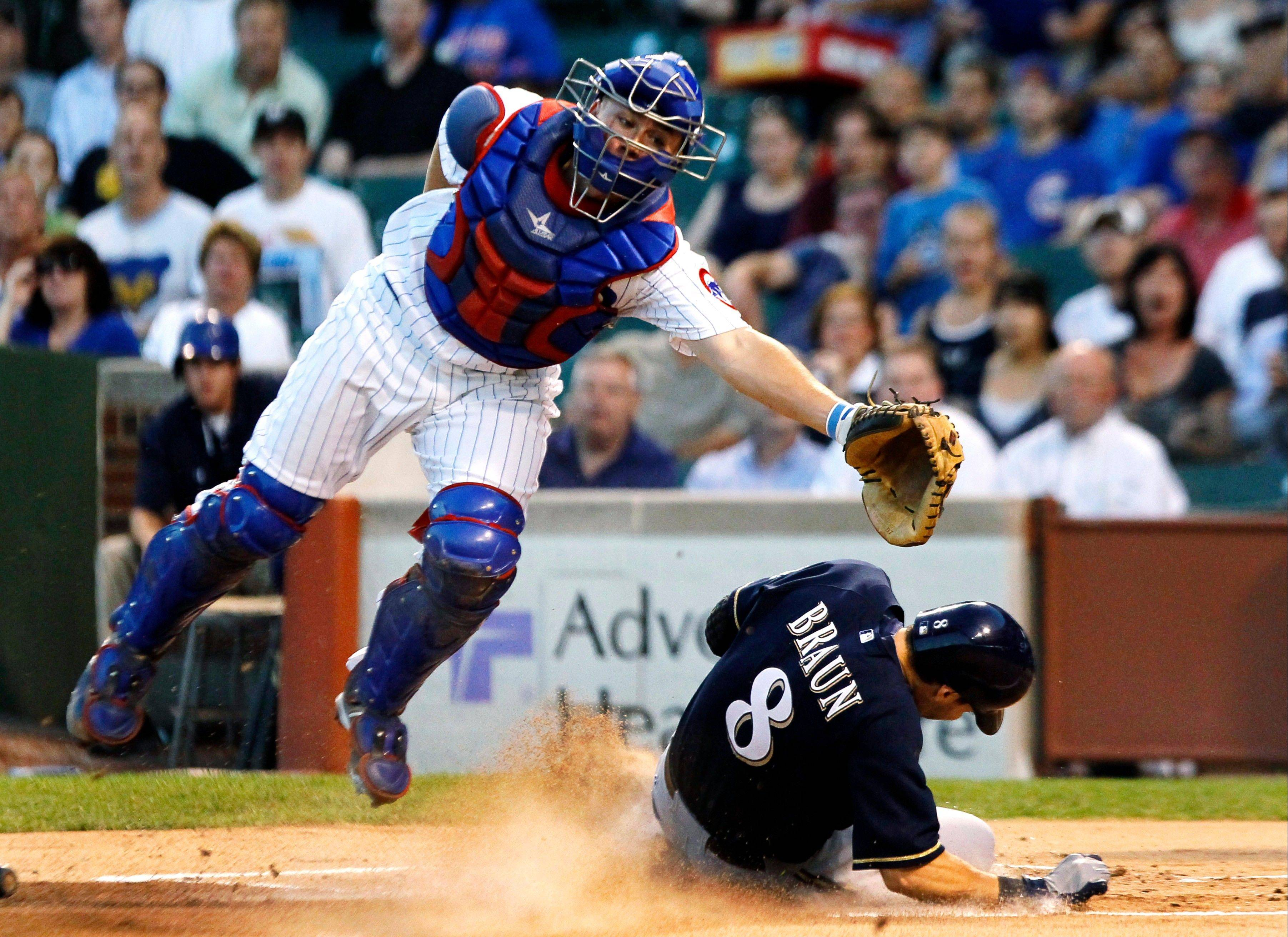Ryan Braun scores on a double by Aramis Ramirez as Cubs catcher Steve Clevender stretches for a wide throw in the first inning Monday at Wrigley Field.