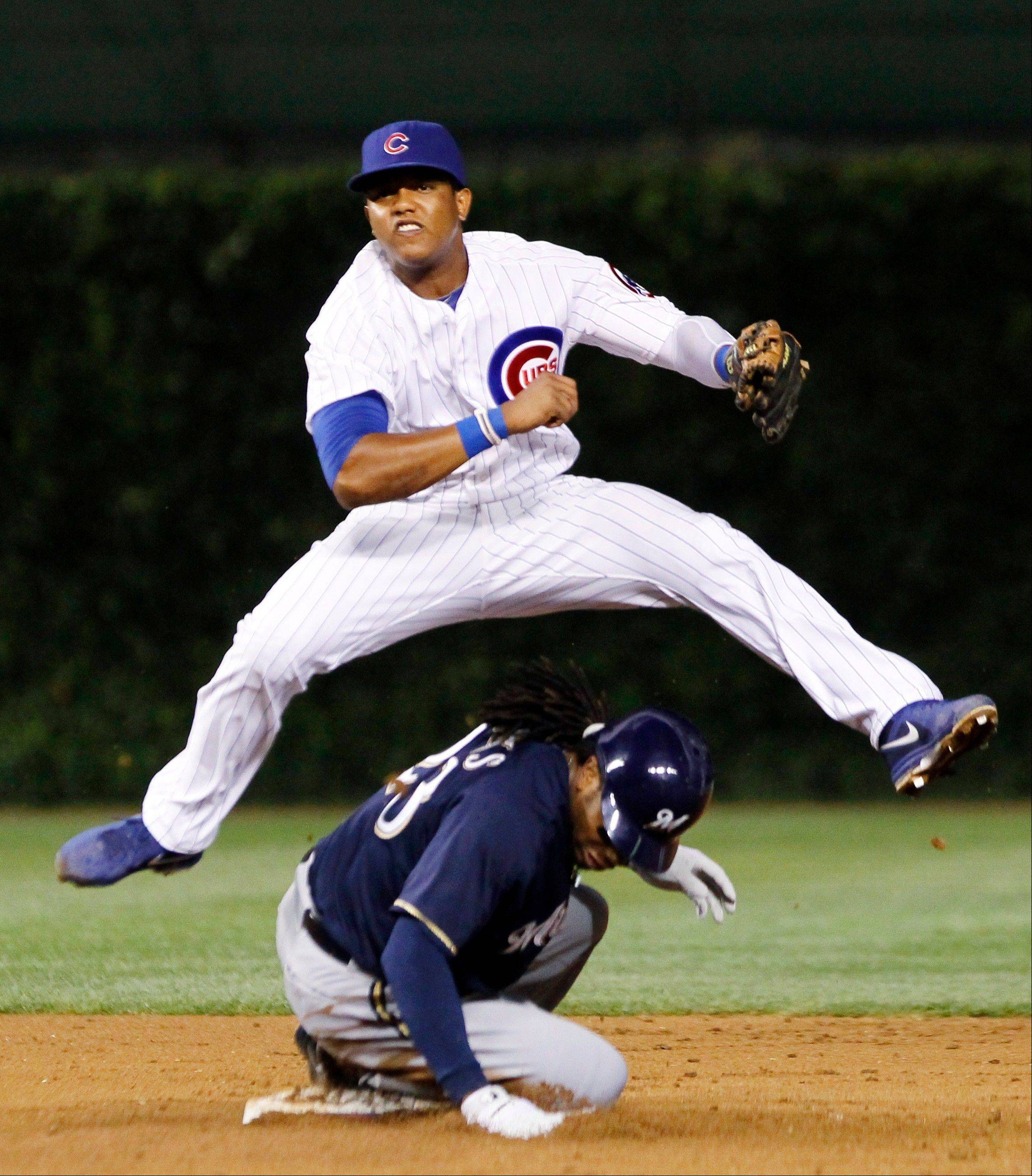 Cubs shortstop Starlin Castro begins a double play, forcing the Milwaukee Brewers' Rickie Weeks at second and getting Ryan Braun at first during the third inning Monday at Wrigley Field.