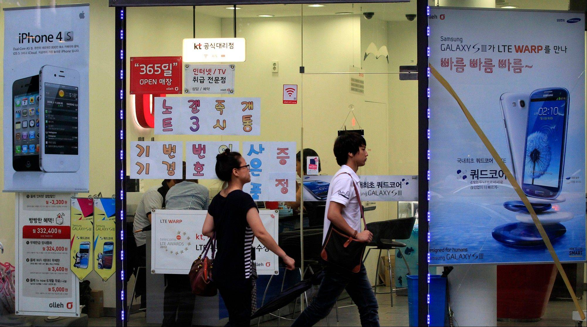 People walk past by banners advertising Samsung and Apple�s smart phones at a mobile phone shop in Seoul, South Korea, Tuesday. A U.S. jury�s $1 billion verdict against Samsung for what rival Apple claimed was the illegal copying of its iPhone and iPad designs signals a turning point for the South Korean electronics giant.