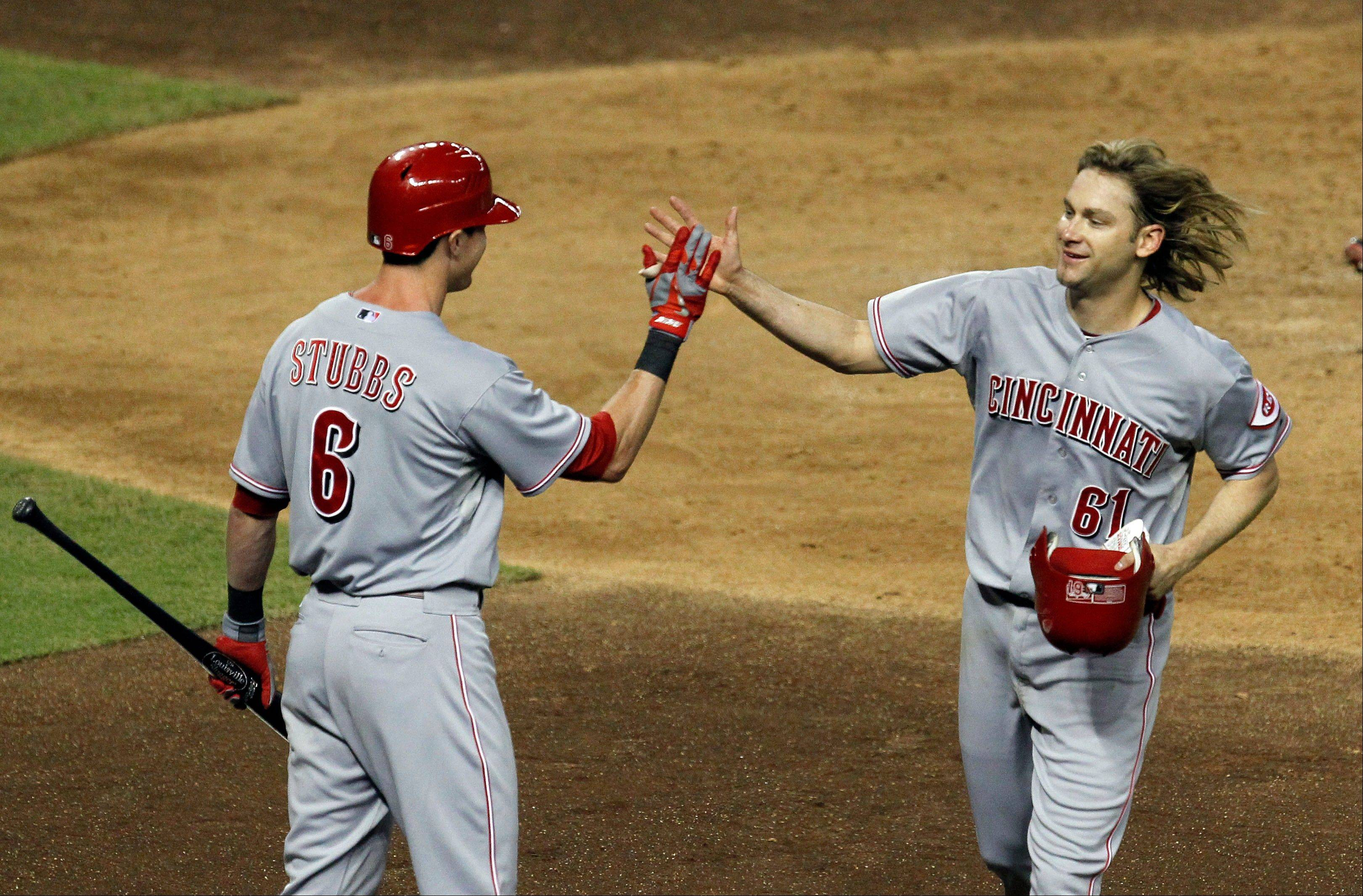 The Reds� Bronson Arroyo gets a high-five from teammate Drew Stubbs after hitting a home run against the Arizona Diamondbacks in the sixth inning Monday in Phoenix.