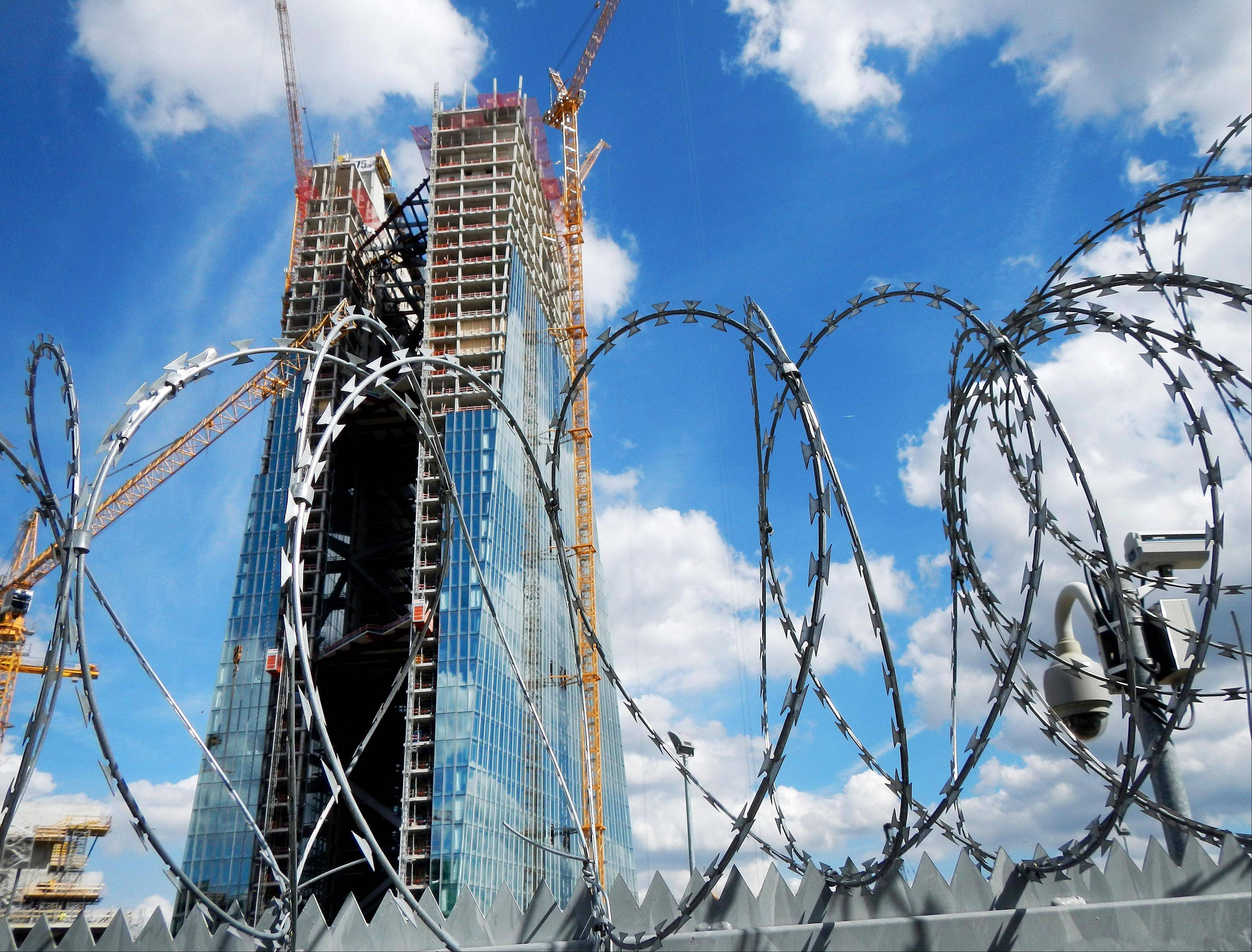 The new headquarter of the European Central Bank rises behind barbed wire in Frankfurt, Germany