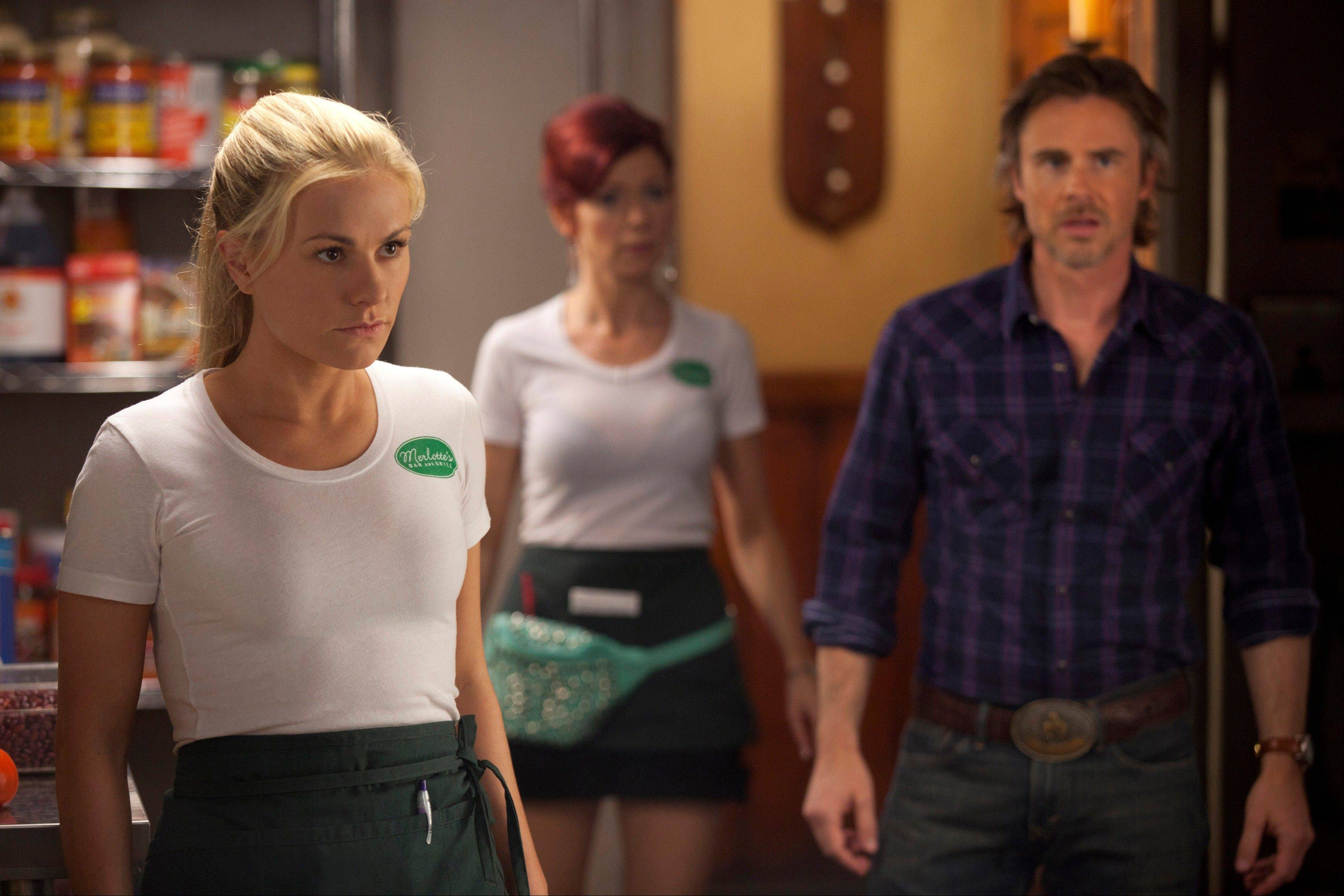 "Anna Paquin as Sookie Stackhouse, Carrie Preston as Arlene Fowler, Sam Trammell as Sam Merlotte in a scene from ""True Blood."" Recipes by Marcelle Bienvenu, inspired by the popular supernatural series, have been gathered in a book ""True Blood: East, Drinks, and Bites from Bon Temps."""