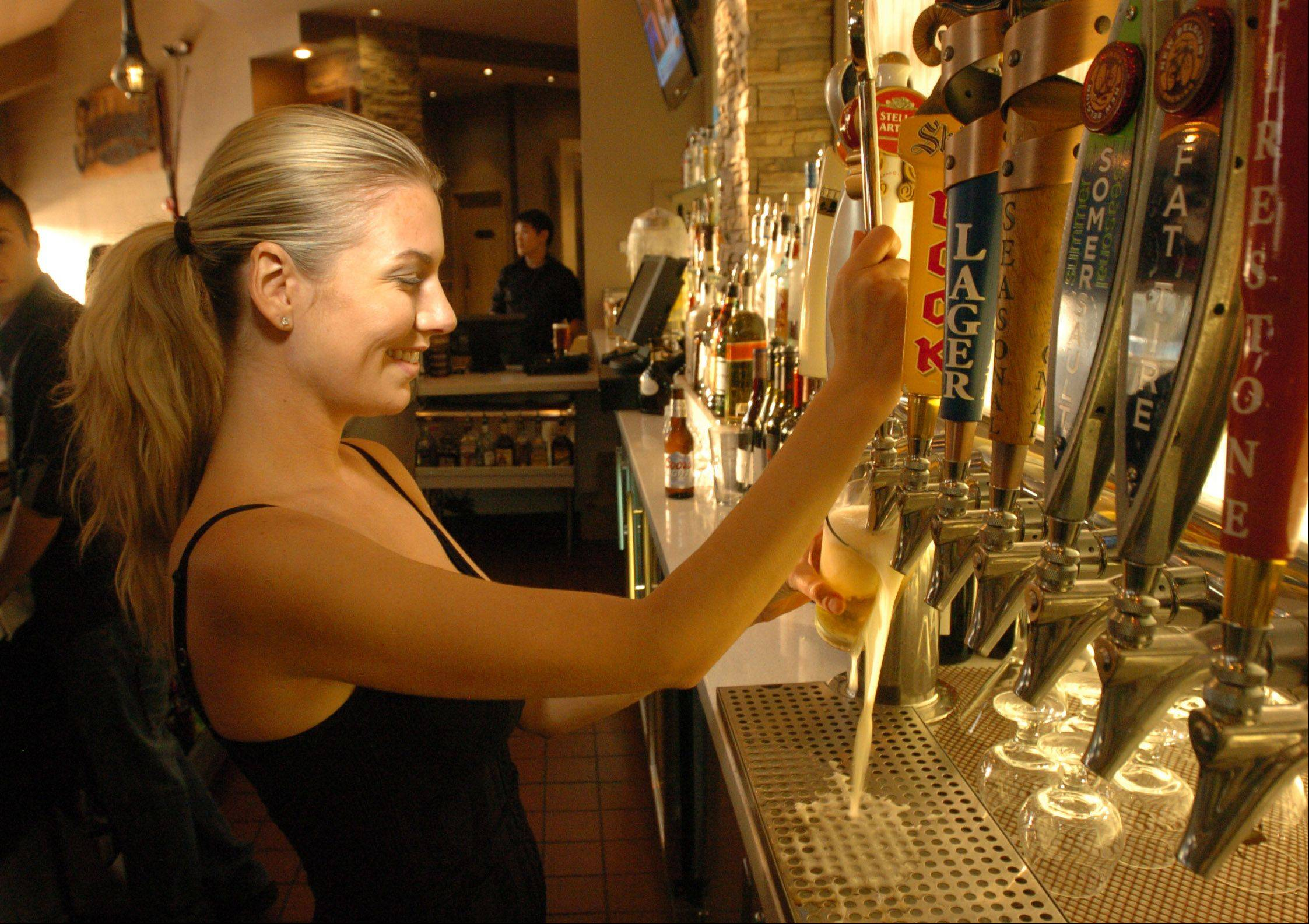 Christine Kaberna taps a beer at Lombard's new Trademark Tavern.