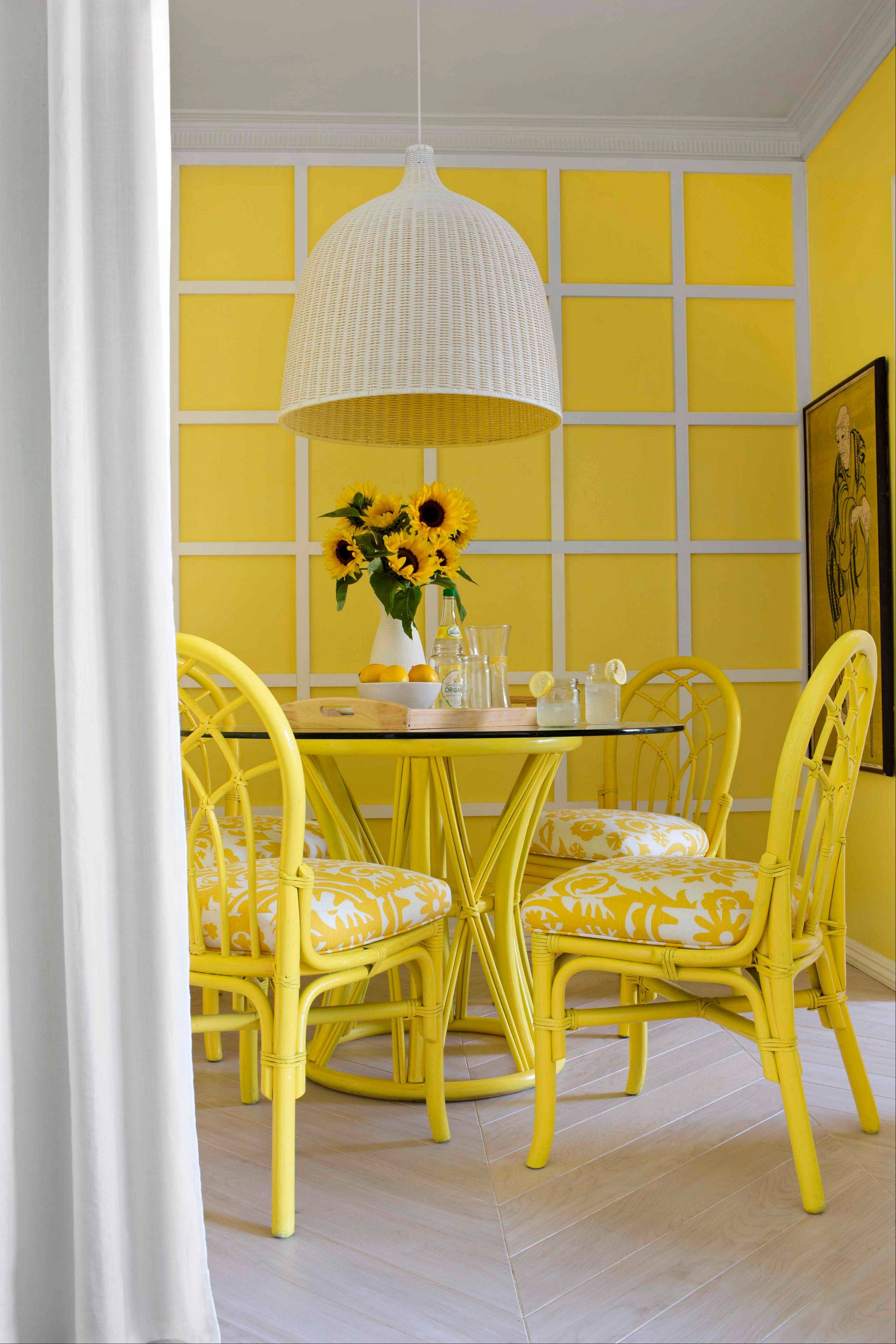 An Australian photographer's love of warm, golden yellow Australian sun from his home country inspired designer Brian Patrick Flynn to cover the entire space in bright yellow tones in his client's dining room in Los Angeles.