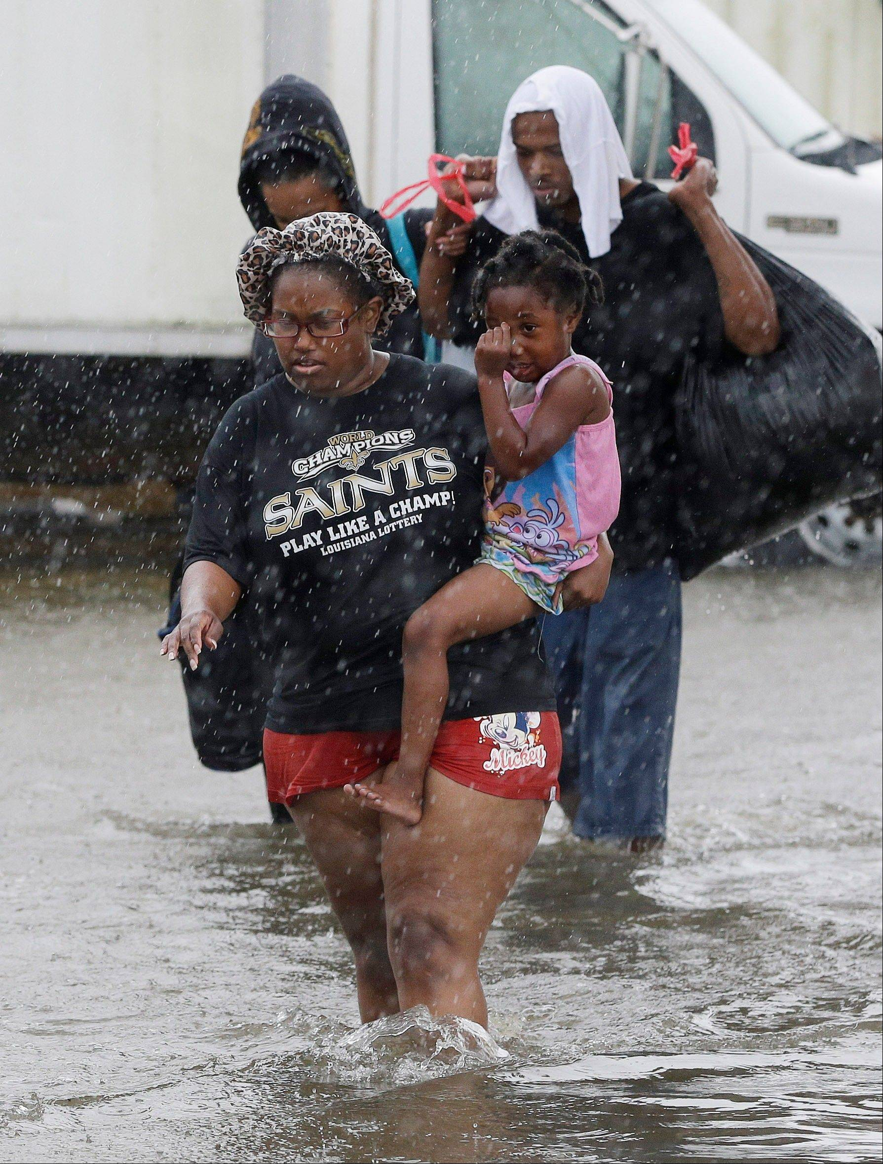 Residents evacuate their flooded neighborhood, Thursday, Aug. 30, 2012, in LaPlace, La.