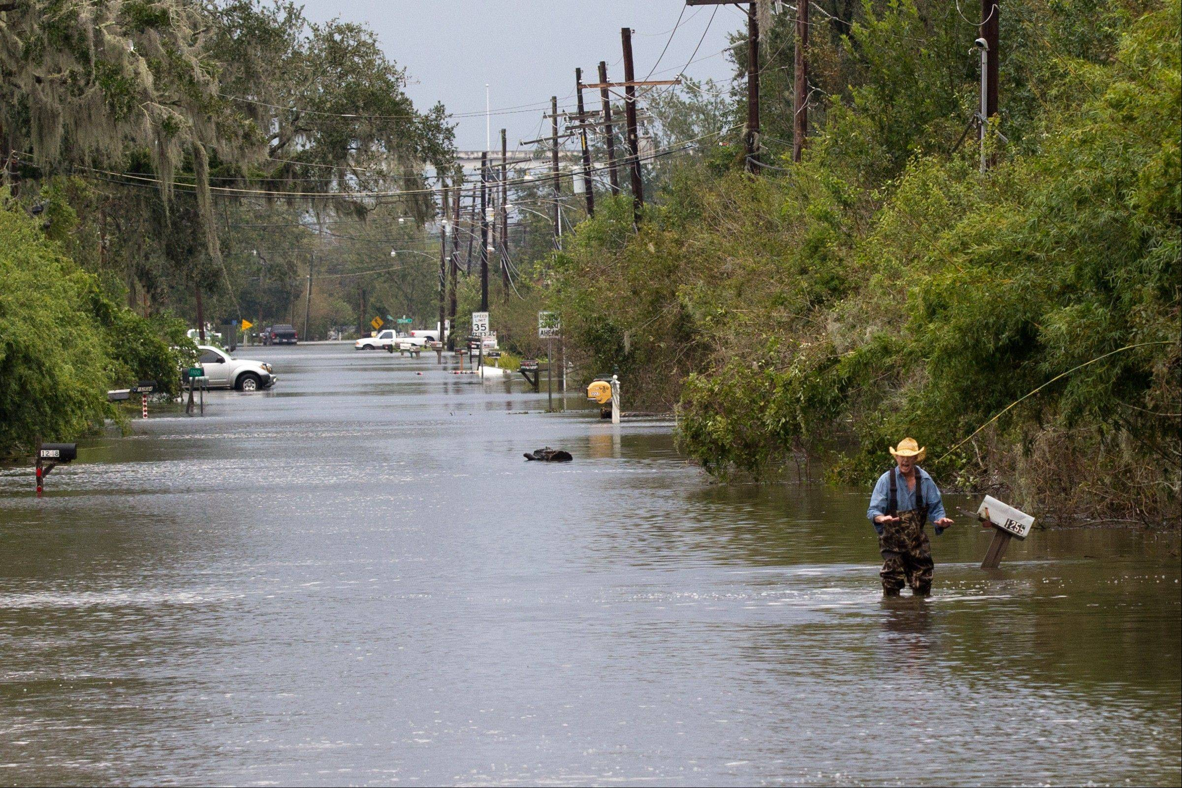 A man gestures at emergency responders' trucks to slow down to prevent a wake of floodwater from entering his home in Lafitte, La., on Thursday, Aug. 30, 2012.