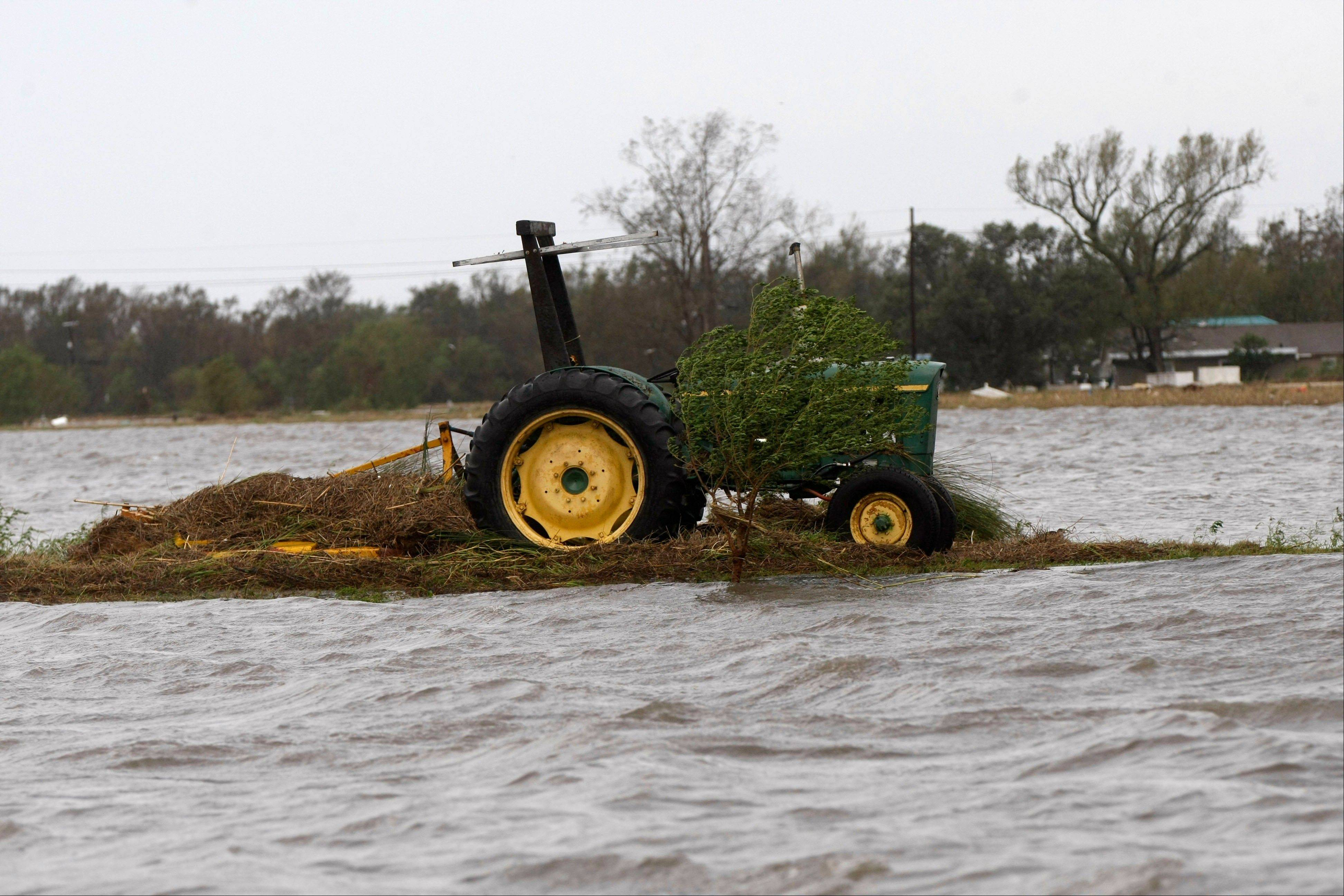A tractor sits safely atop a mound, after Isaac passed through the region, in Plaquemines Parish, La., Thursday, Aug. 30, 2012.