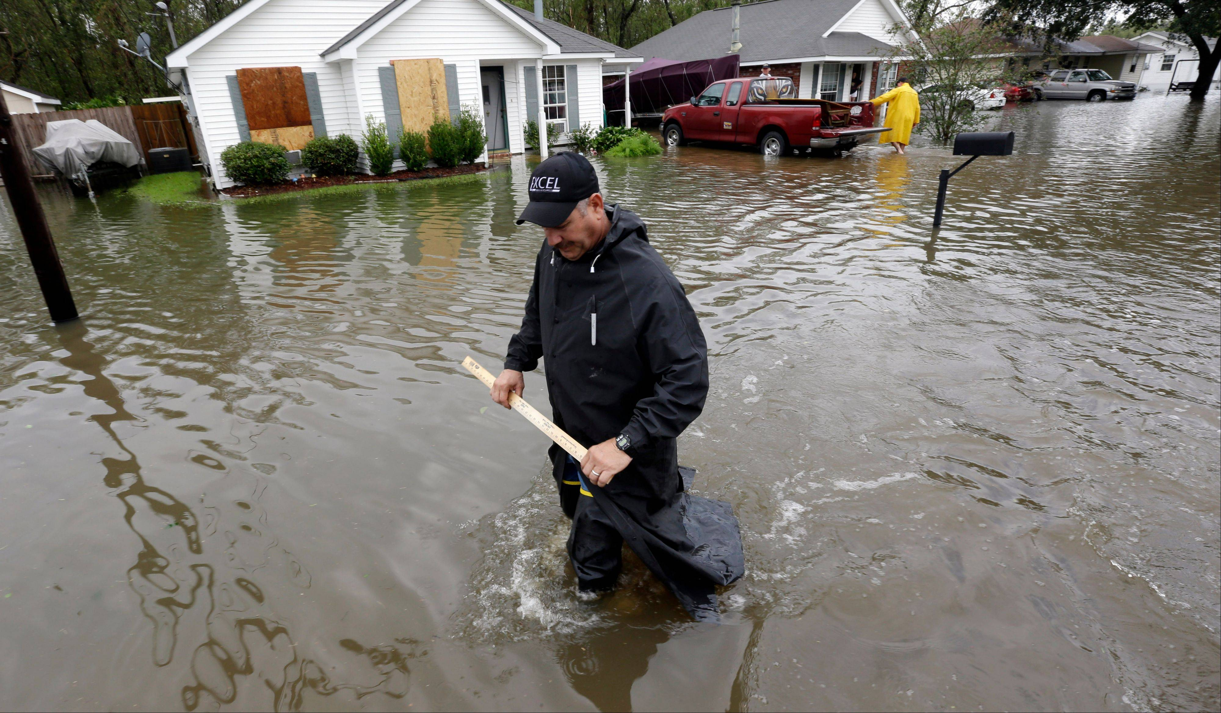 Myron Romondet takes measurements of the flood waters on his street, Thursday, Aug. 30, 2012, in LaPlace, La.