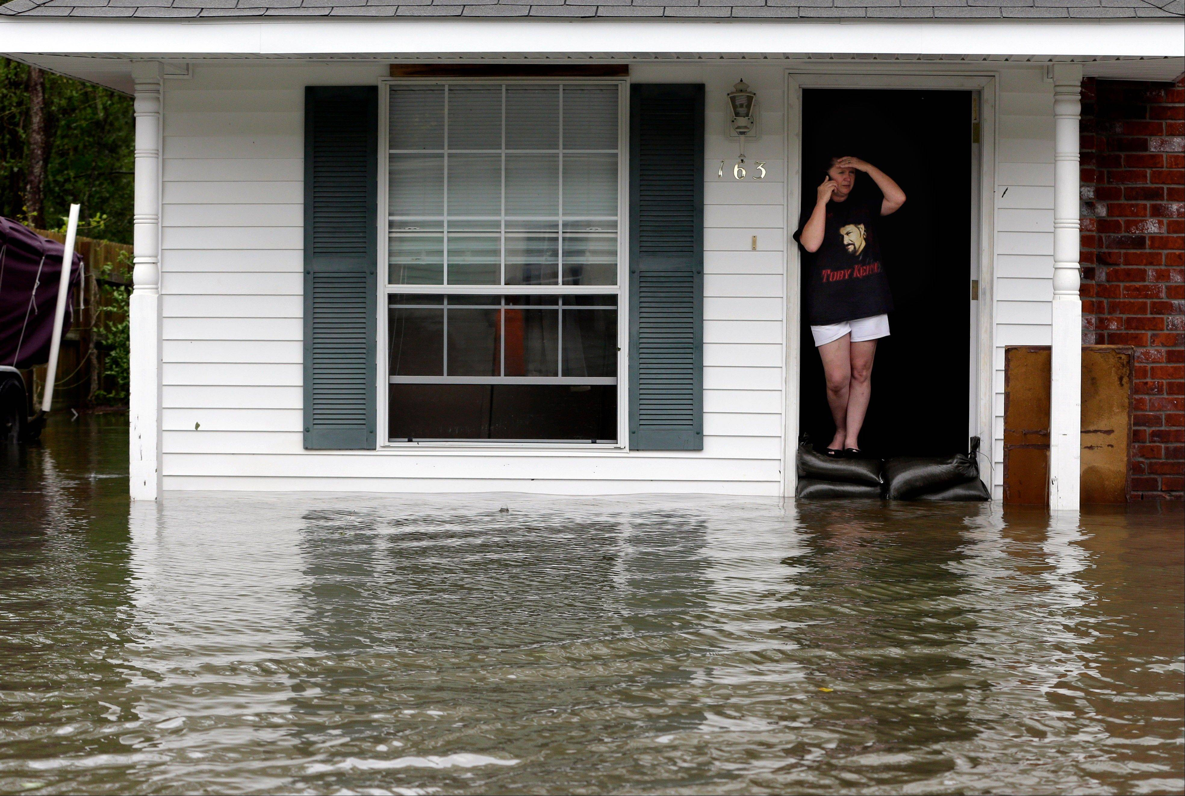 A resident whose home is surrounded by flood waters talks on the phone, Thursday, Aug. 30, 2012, in LaPlace, La.
