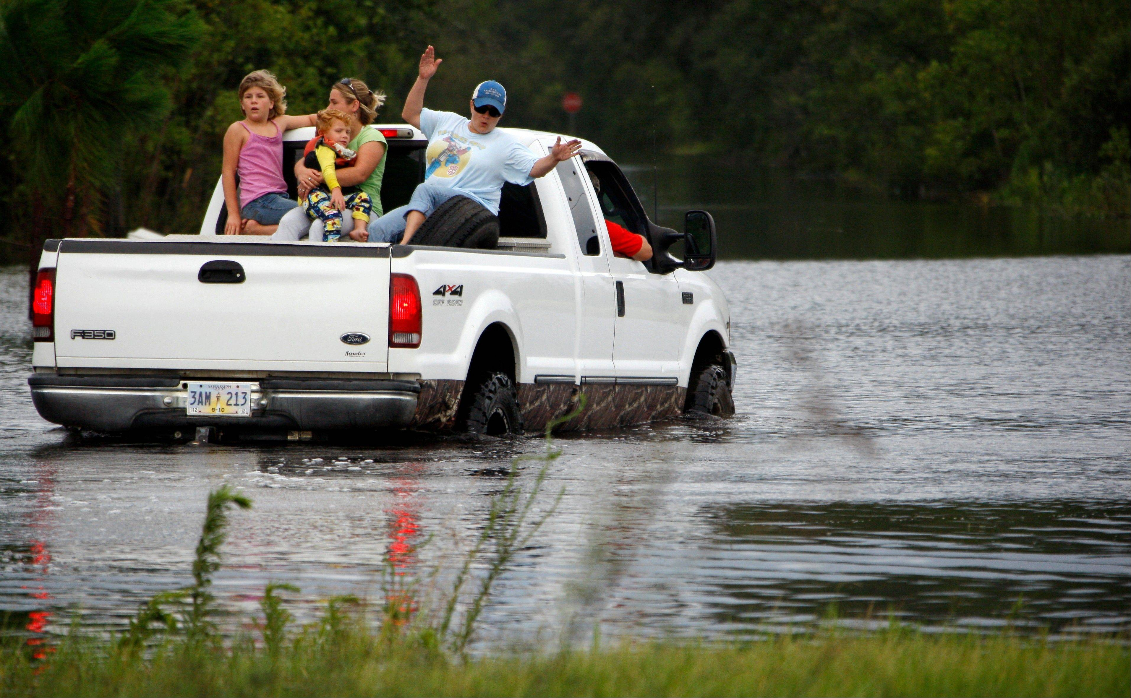 Waveland, Miss., residents ride through storm waters left from Isaac's unceasing rainstorms, Thursday, Aug. 30, 2012.