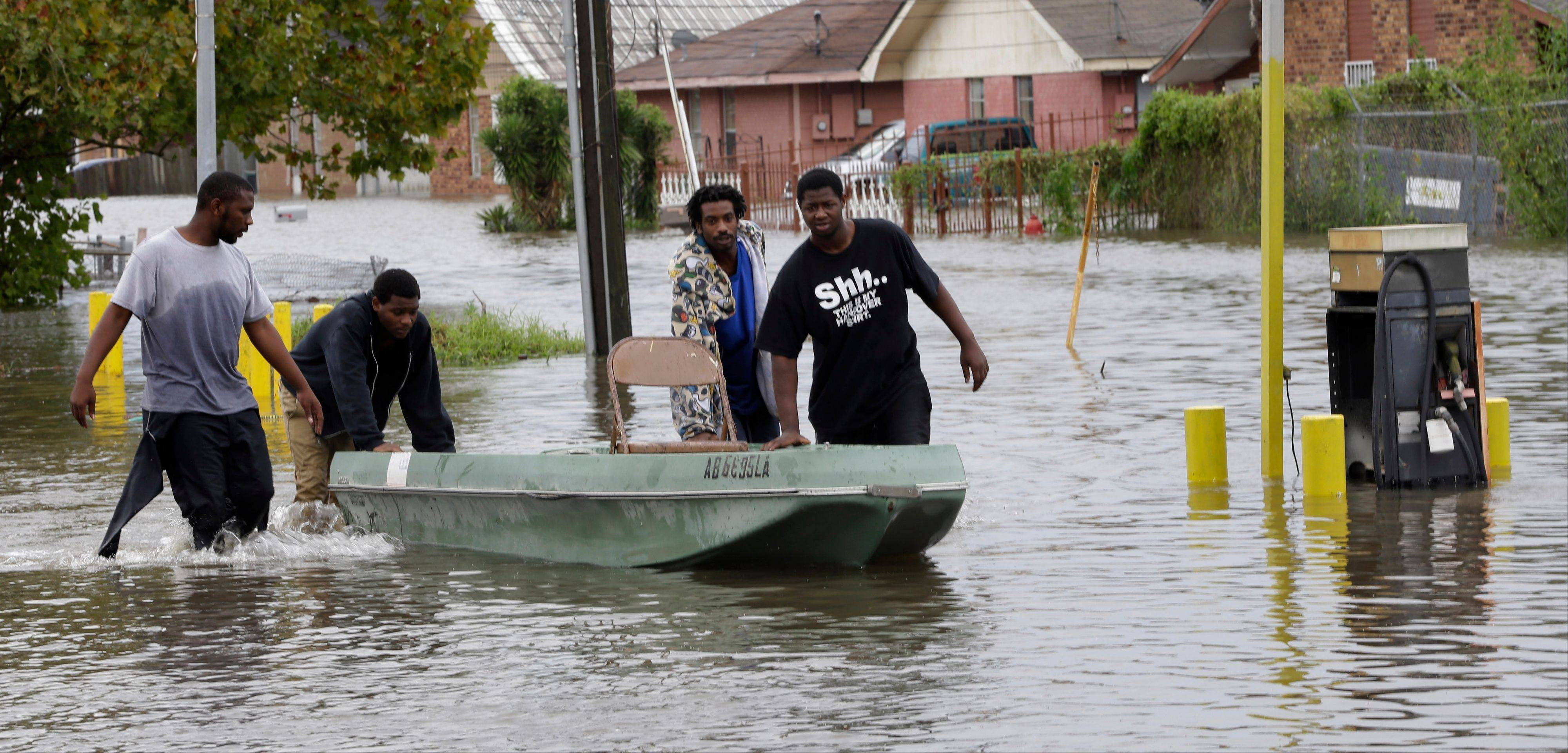 Residents use a boat to navigate their flooded neighborhood, Thursday, Aug. 30, 2012, in LaPlace, La.