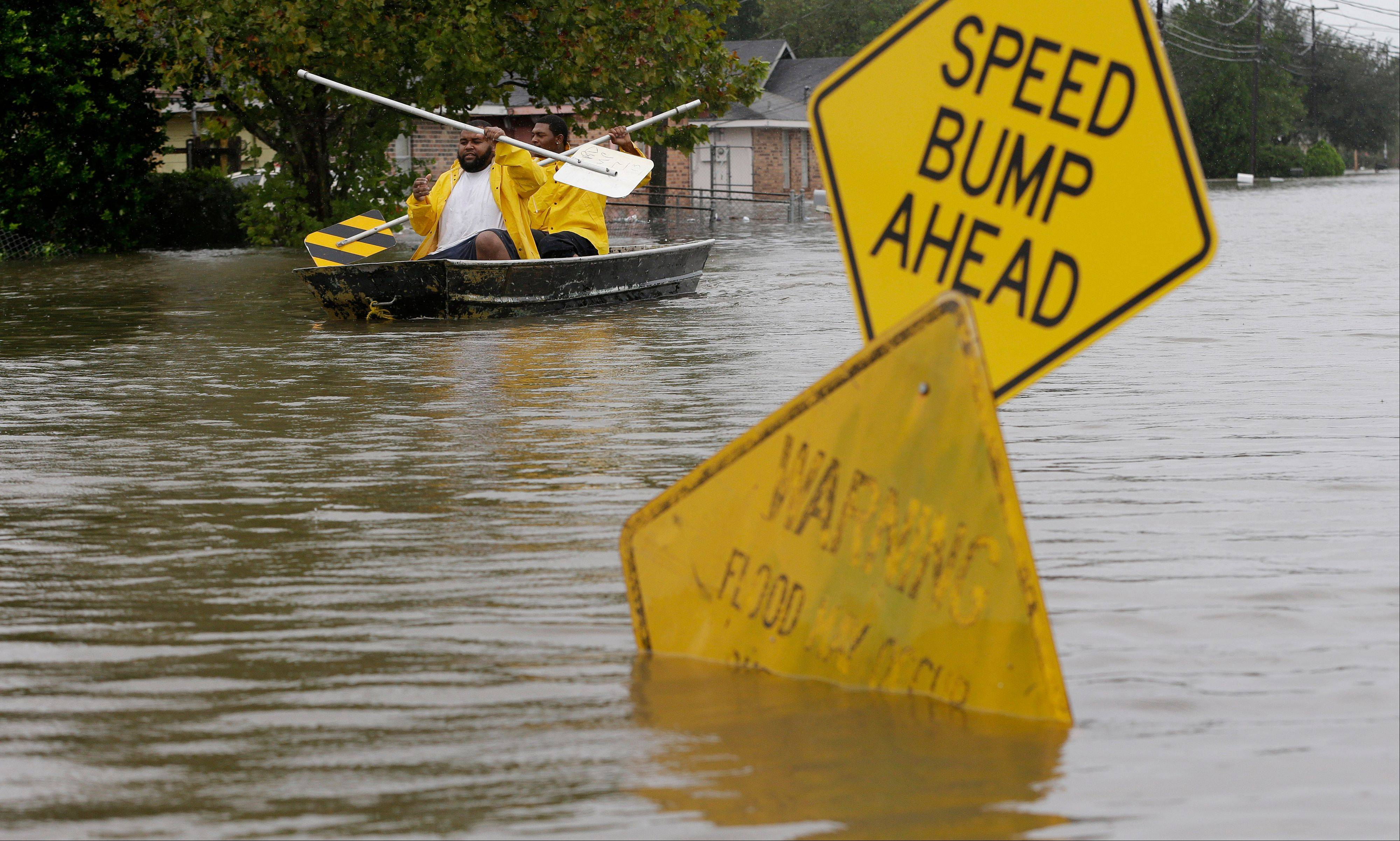 Isaac Fields, left, and Victor Jones use street signs to paddle a boat out of their flooded neighbor, Thursday, Aug. 30, 2012, in LaPlace, La.