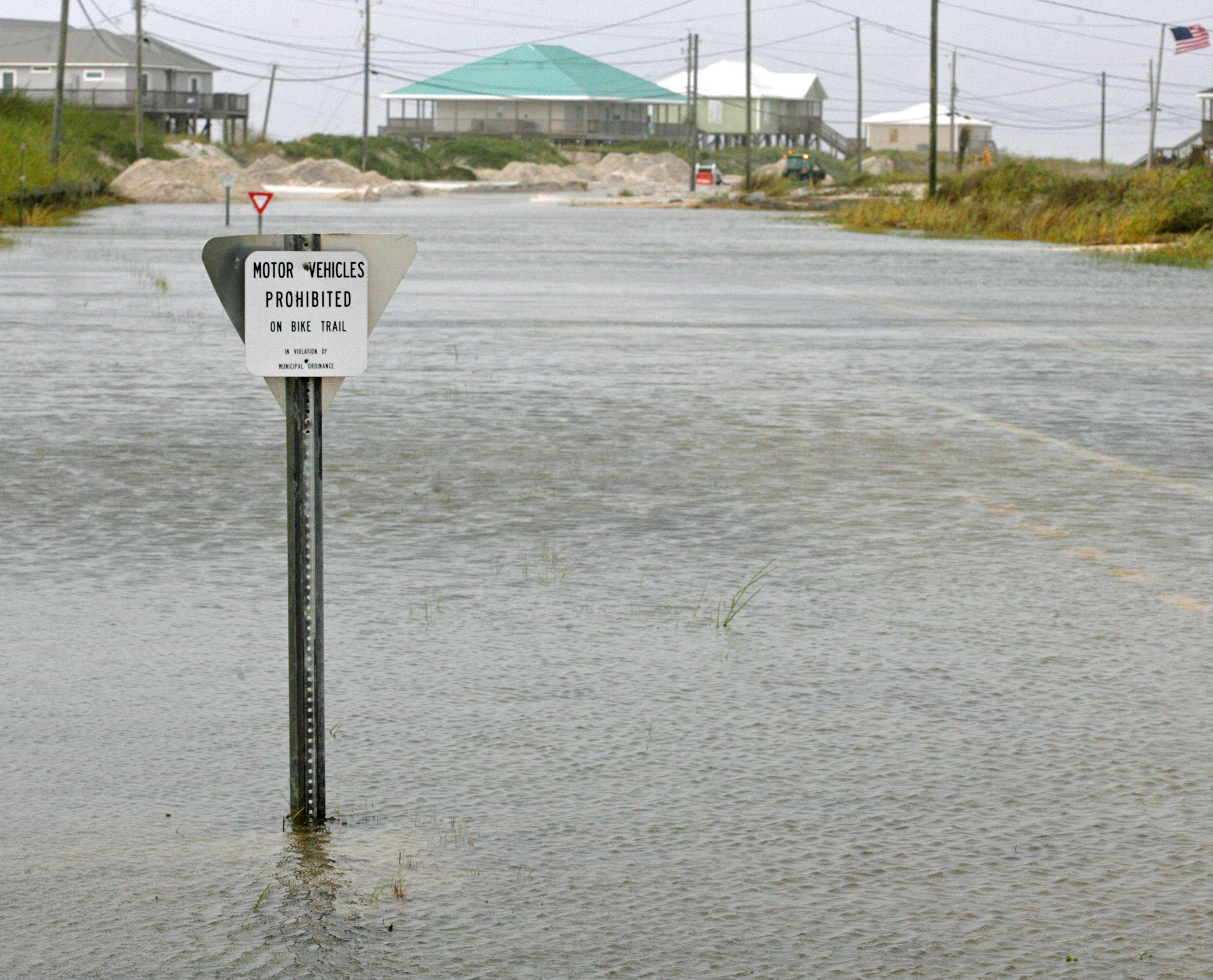 A sign prohibiting motor vehicles on the island's bicycle trial is now surrounded by flood waters that also cover Bienville Blvd., Thursday, Aug. 30, 2012 on Dauphin Island, Ala.
