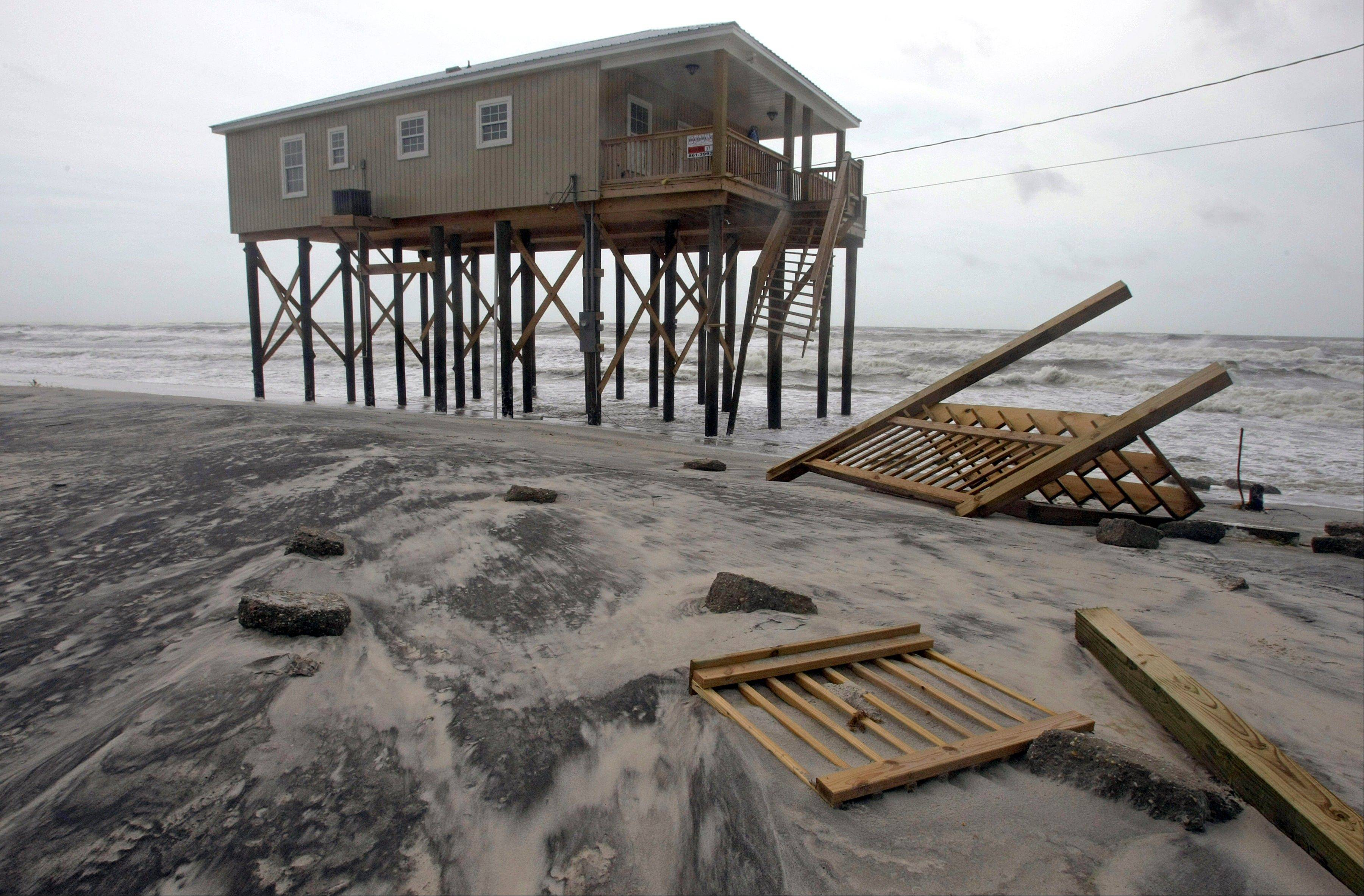 The staircase for a home now lies smashed in the sands in front of the structure Thursday, Aug. 30, 2012 on Dauphin Island, Ala. after Hurricane Isaac's landfall in Louisiana.