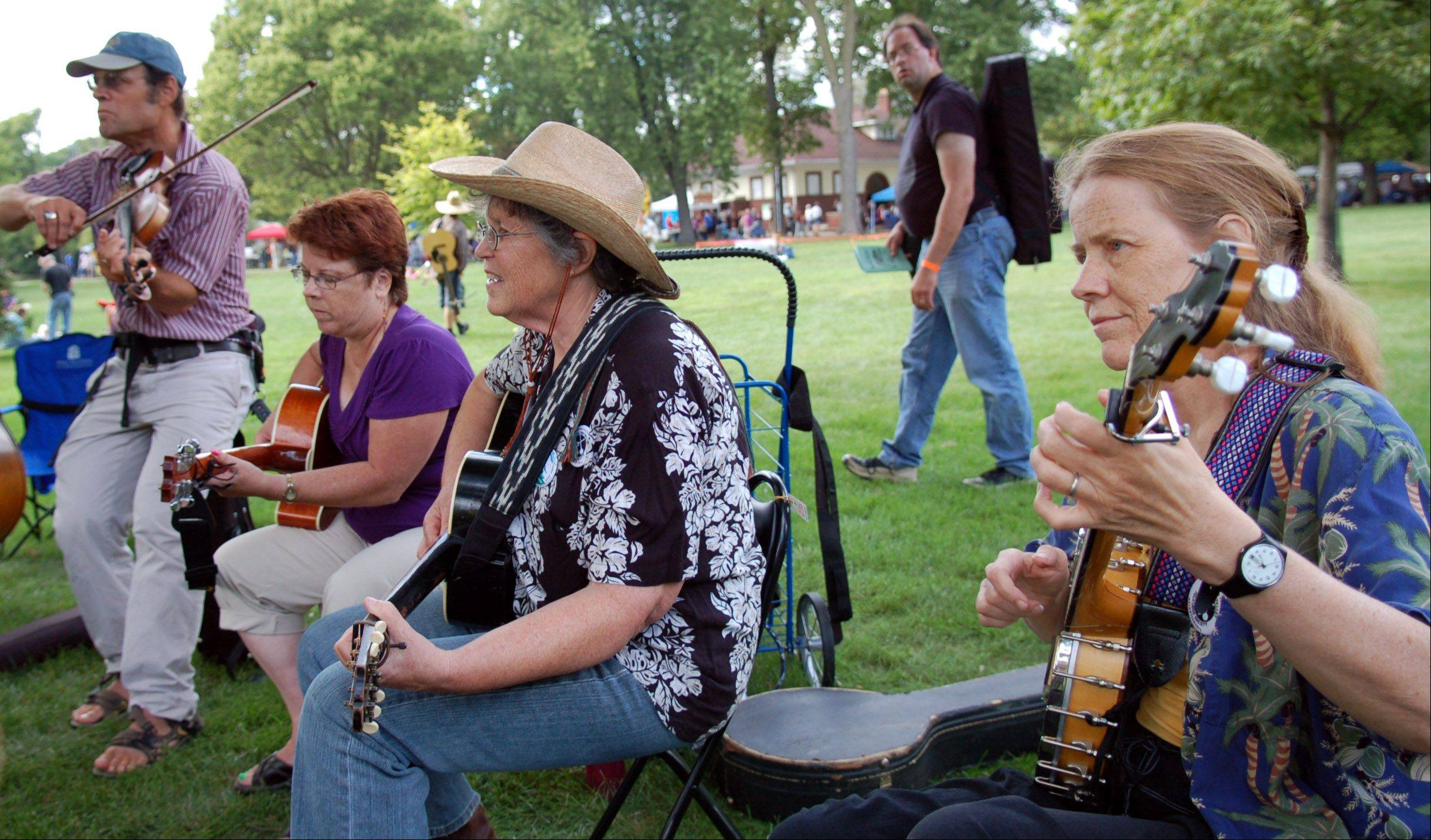 A group of musicians play folk music during last year's 35th Fox Valley Folk Music and Storytelling Festival at Island Park on the Fox River in Geneva. The group meets up every year to play together; some are old friends and some are new.