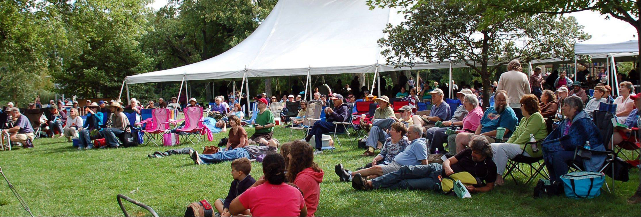 Visitors enjoy sitting in front of the main stage and listening to live folk music all afternoon during the 35th Fox Valley Folk Music & Storytelling Festival at Island Park in Geneva.