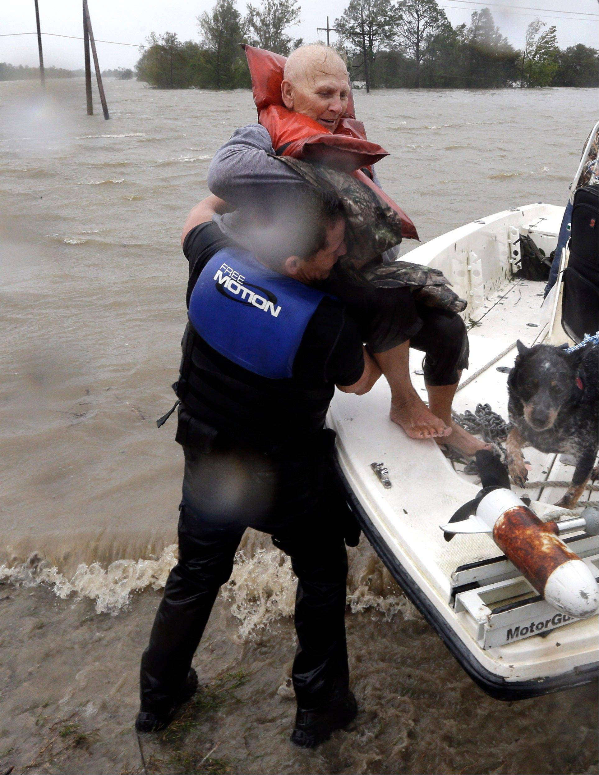 Elaine Maltese is lifted out of a boat by by Drug Enforcement Agency Special Agent Keith Billiot, left, after being rescued from her flooded home as Hurricane Isaac hits Wednesday, Aug. 29, 2012, in Braithwaite, La.