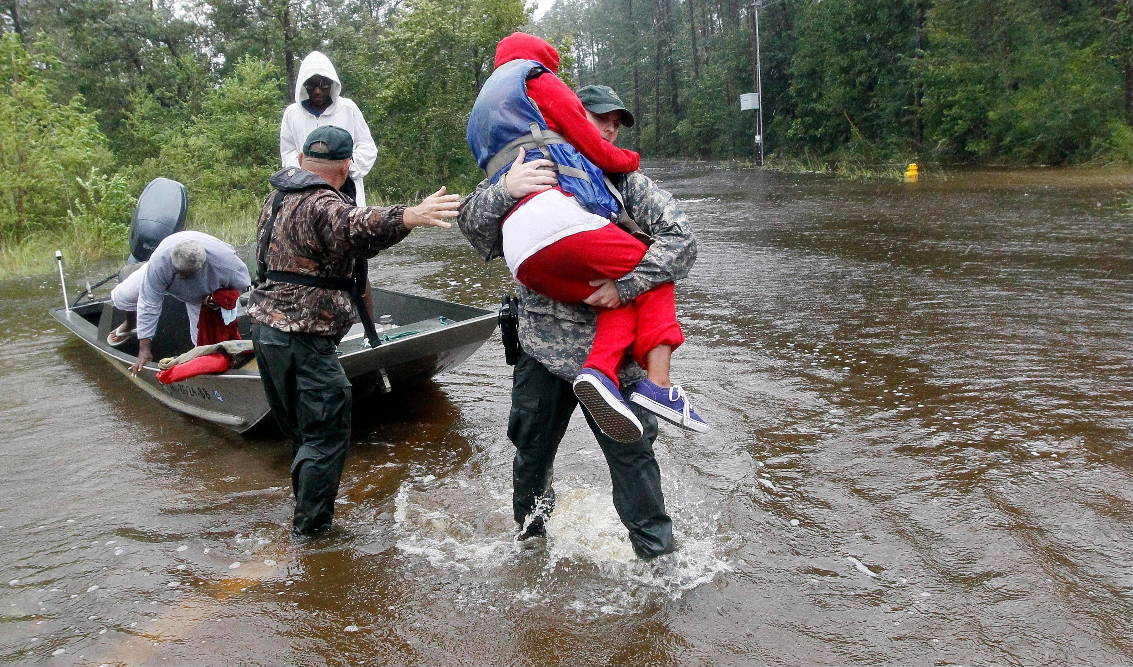 Law enforcement officers and first responders help a family to reach dry land after they were rescued from floodwaters caused by Isaac in Pearlington, Miss., Wednesday, Aug. 29, 2012, during a nonstop rain.