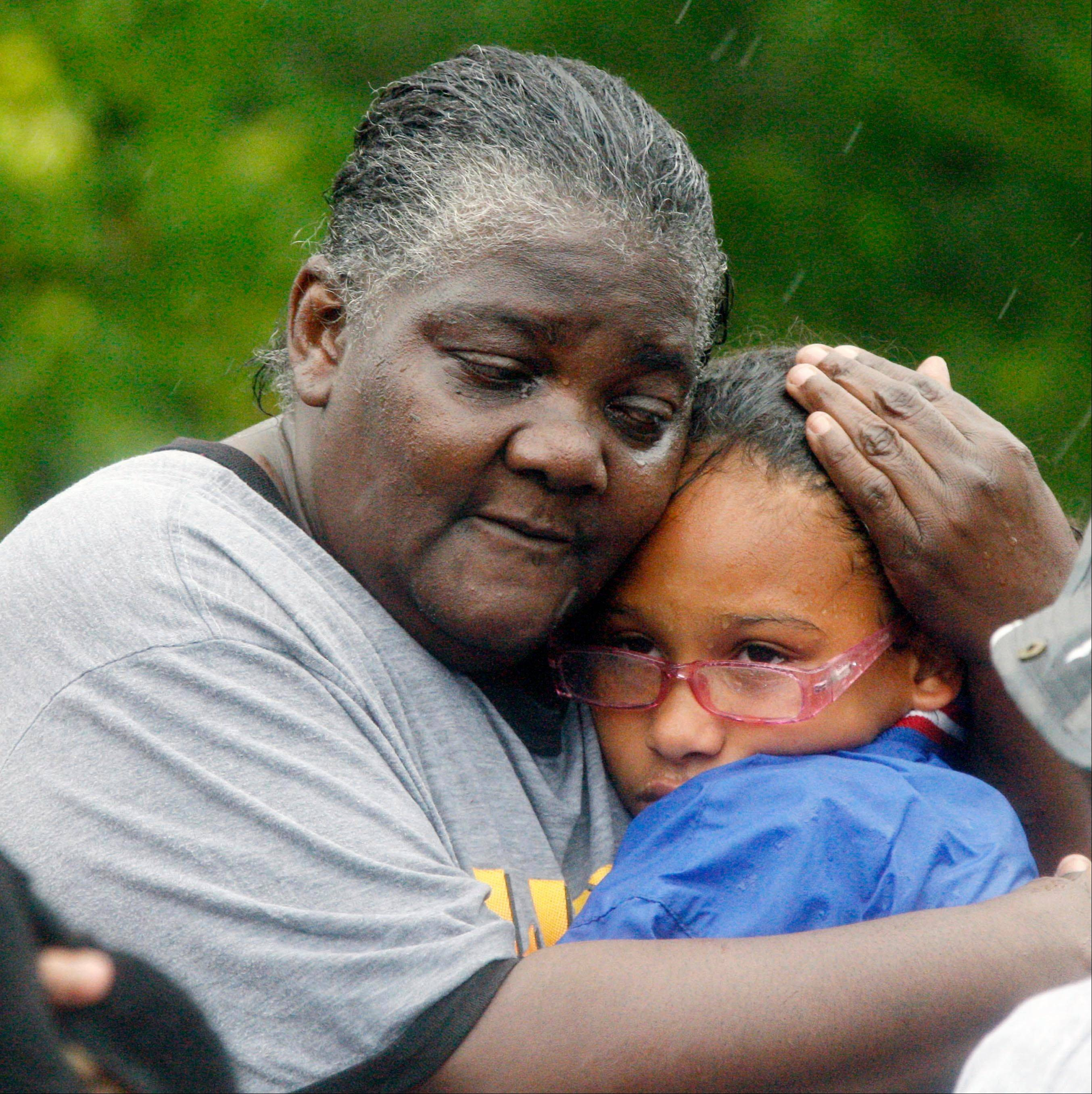 Danessa Lee, left, comforts her granddaughter Ashanti Lee, 12, after their family was rescued in Pearlington, Miss., by law enforcement officers and first responders using boats, Wednesday, Aug. 29, 2012, during the nonstop rain from Isaac.