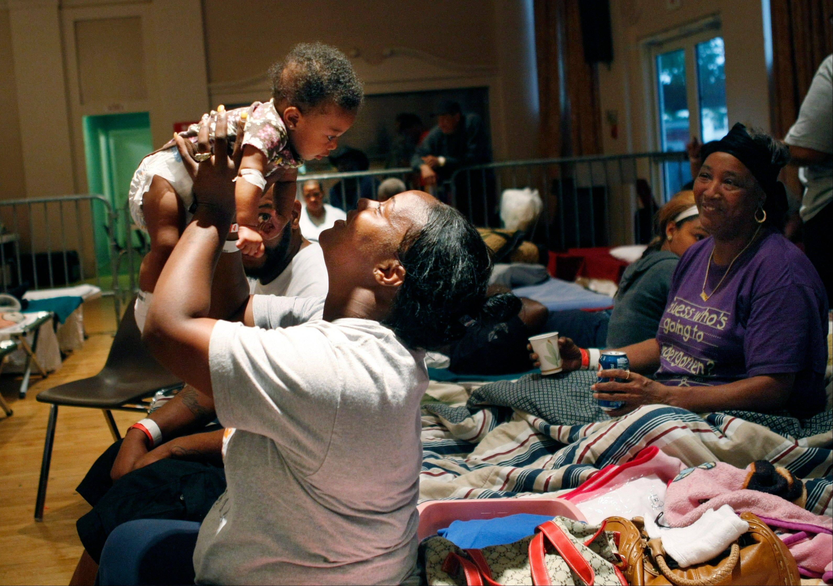 Toccara Williams, of Davant, La., holds her 5-month-old daughter Ra-Maaz Williams, at an evacuation shelter after Isaac made landfall as a Hurricane, in Belle Chasse, La., Wednesday, Aug. 29, 2012.