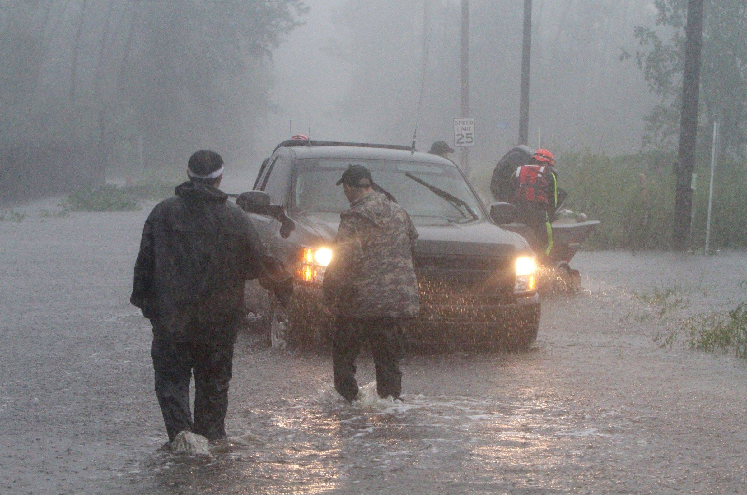 Members of the Swift Water Rescue Team launch a boat to rescue employees of WQRZ radio station in Shoreline Park area of Bay St. Louis, Miss., during Hurricane Isaac on Wednesday Aug. 29, 2012.
