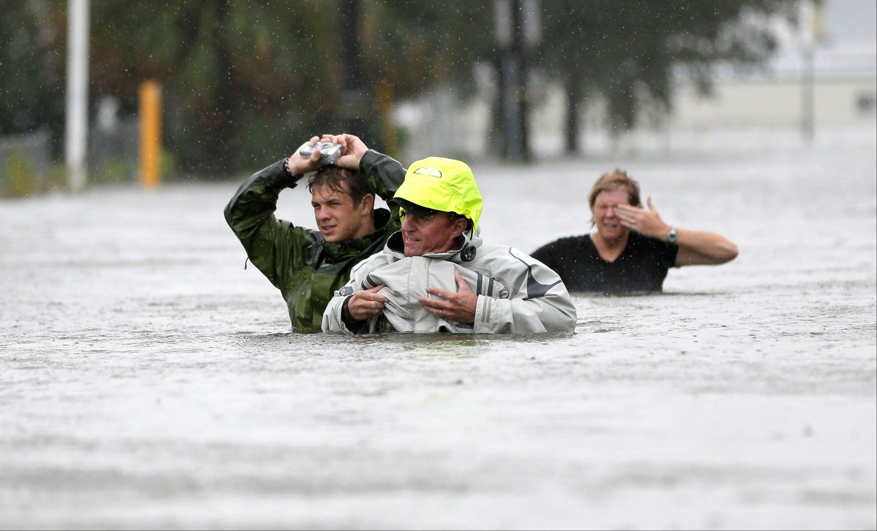 Chuck Cropp, center, his son Piers, left, and wife Liz, right, wade through floodwaters from Hurricane Isaac Wednesday, Aug. 29, 2012, in New Orleans.