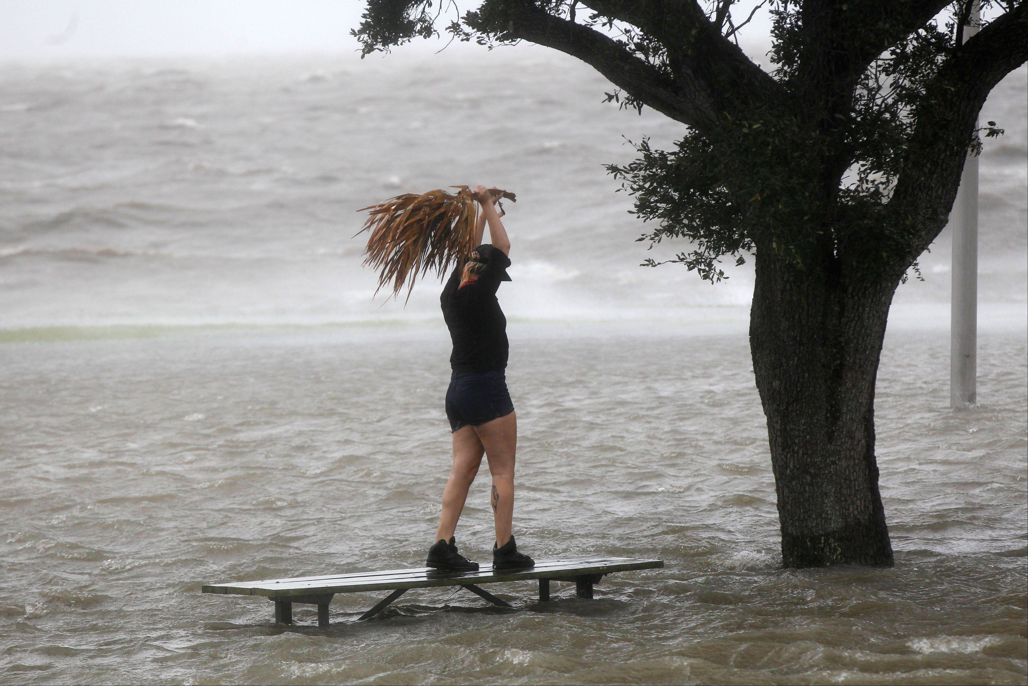 A woman stands on a partially submerged picnic bench in the storm surge from Isaac, on Lakeshore Drive along Lake Pontchartrain, as the storm approaches landfall, in New Orleans, Tuesday, Aug. 28, 2012.