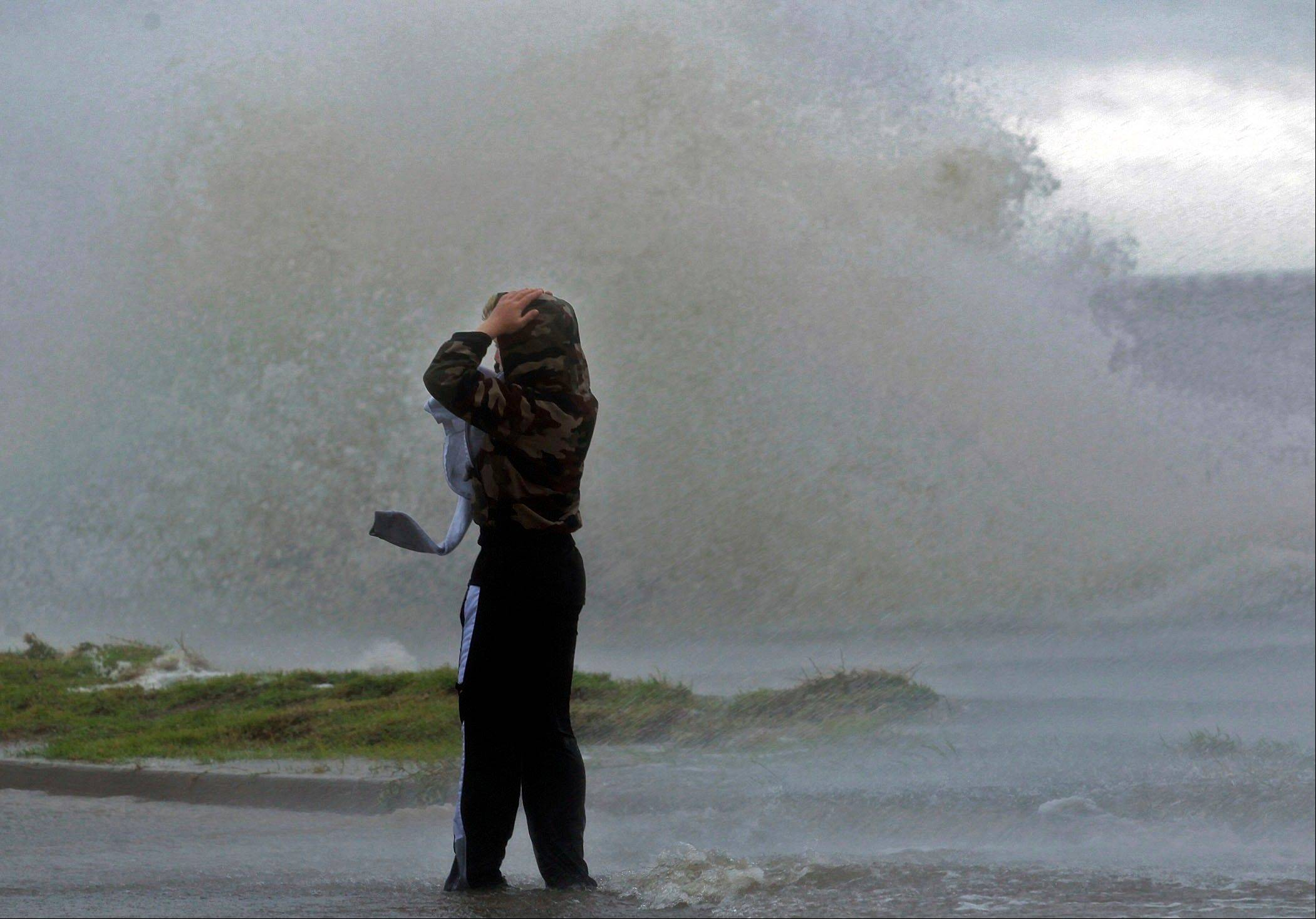Matthew Nicaud braves the wind as waves crash over the seawall of Lake Pontchartrain at Canal Boulevard in New Orleans,Tuesday, Aug. 28, 2012 as Isaac approaches.