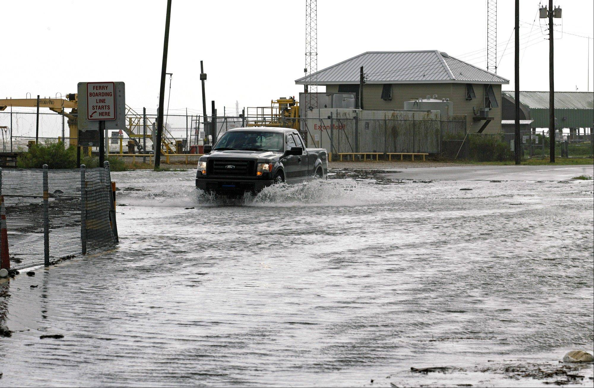 A truck makes its way along flooded Bienville Blvd. at the Dauphin Island Ferry landing Tuesday, Aug. 28, 2012 in Dauphin Island, Ala. as residents prepare for the landfall of Hurricane Isaac along the Gulf Coast.