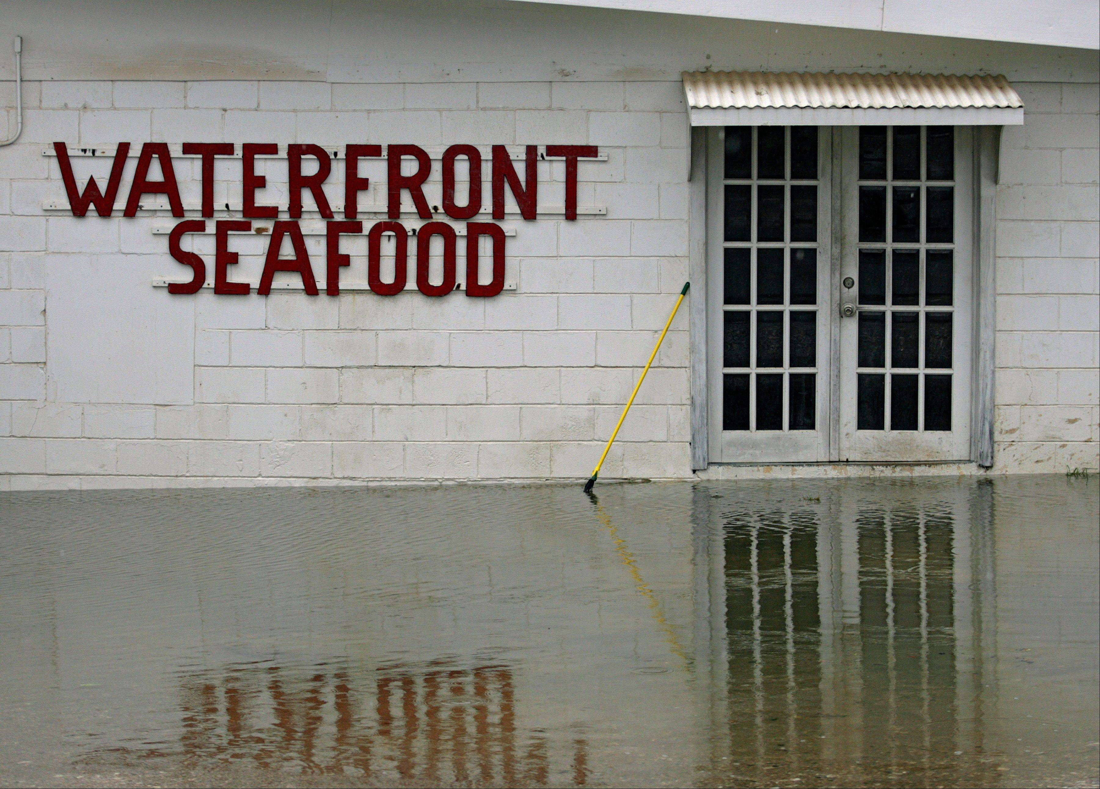 The waters of Bayou La Batre surround the front doors of Waterfront Seafood Tuesday, Aug. 28, 2012 in Bayou La Batre, Ala.