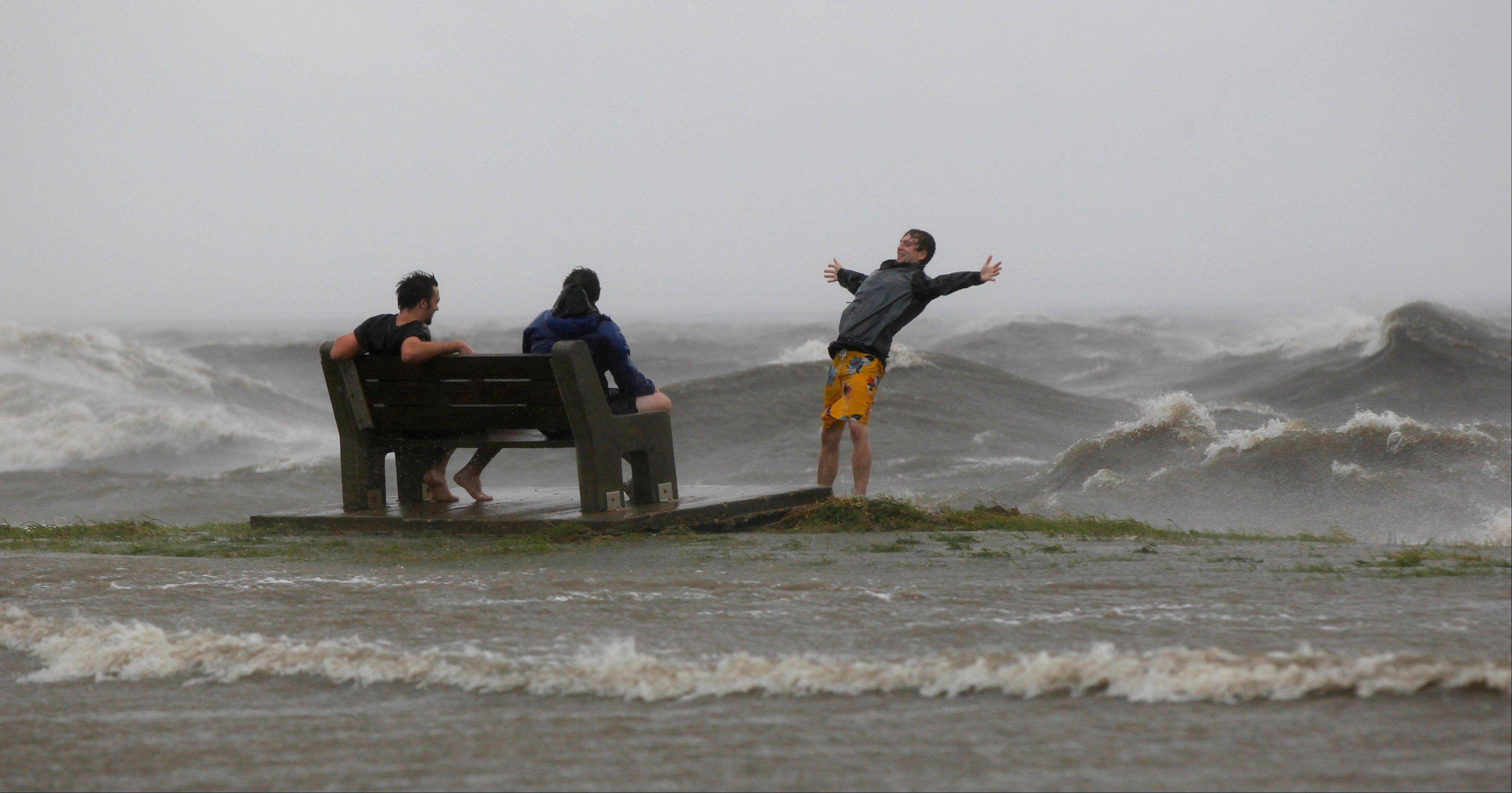 People play in the storm surge from Hurricane Isaac, on Lakeshore Drive along Lake Pontchartrain, as the storm nears land, in New Orleans, Tuesday, Aug. 28, 2012.