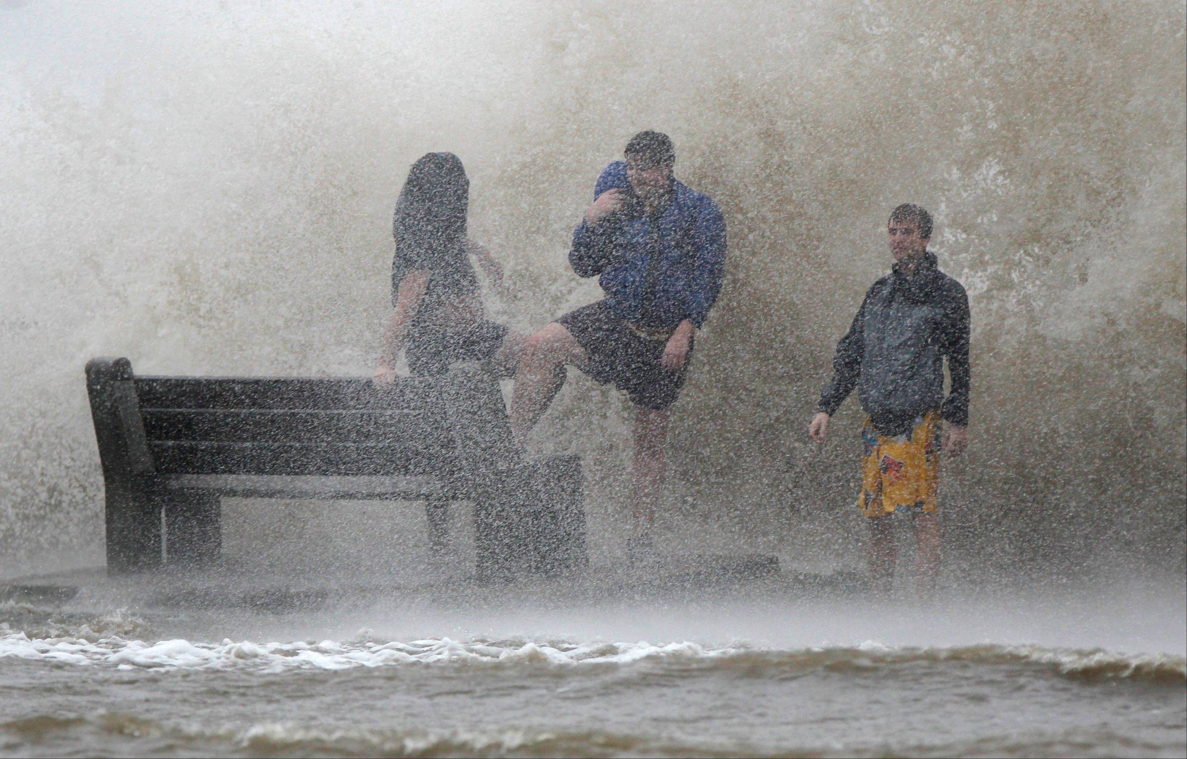 People walk in the storm surge from Isaac, on Lakeshore Drive along Lake Pontchartrain, as the storm approaches landfall, in New Orleans, Tuesday, Aug. 28, 2012.