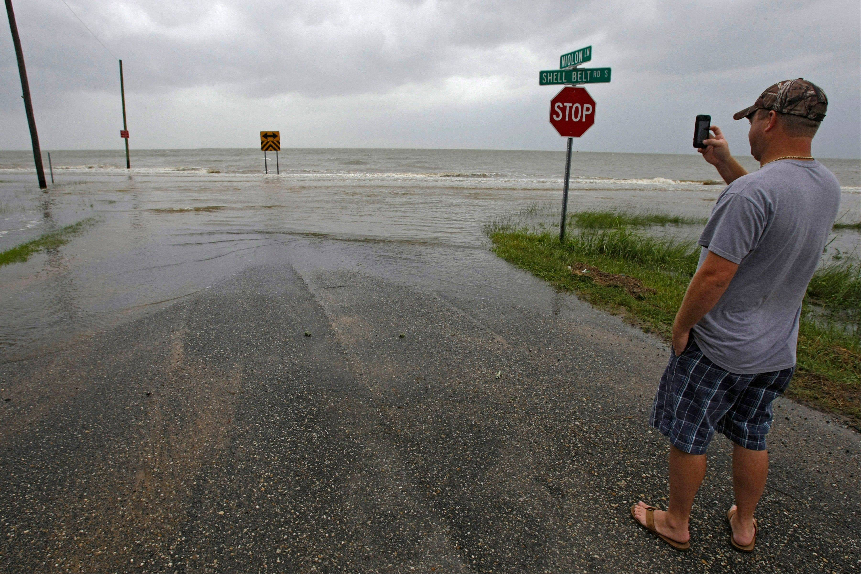 Kevin Clark of Irvington uses his smart phone to photograph the rising waters of the Mississippi sound as they push on to Shell Belt Road at Niolon Lane Tuesday, Aug. 28, 2012 in Bayou La Batre, Ala.