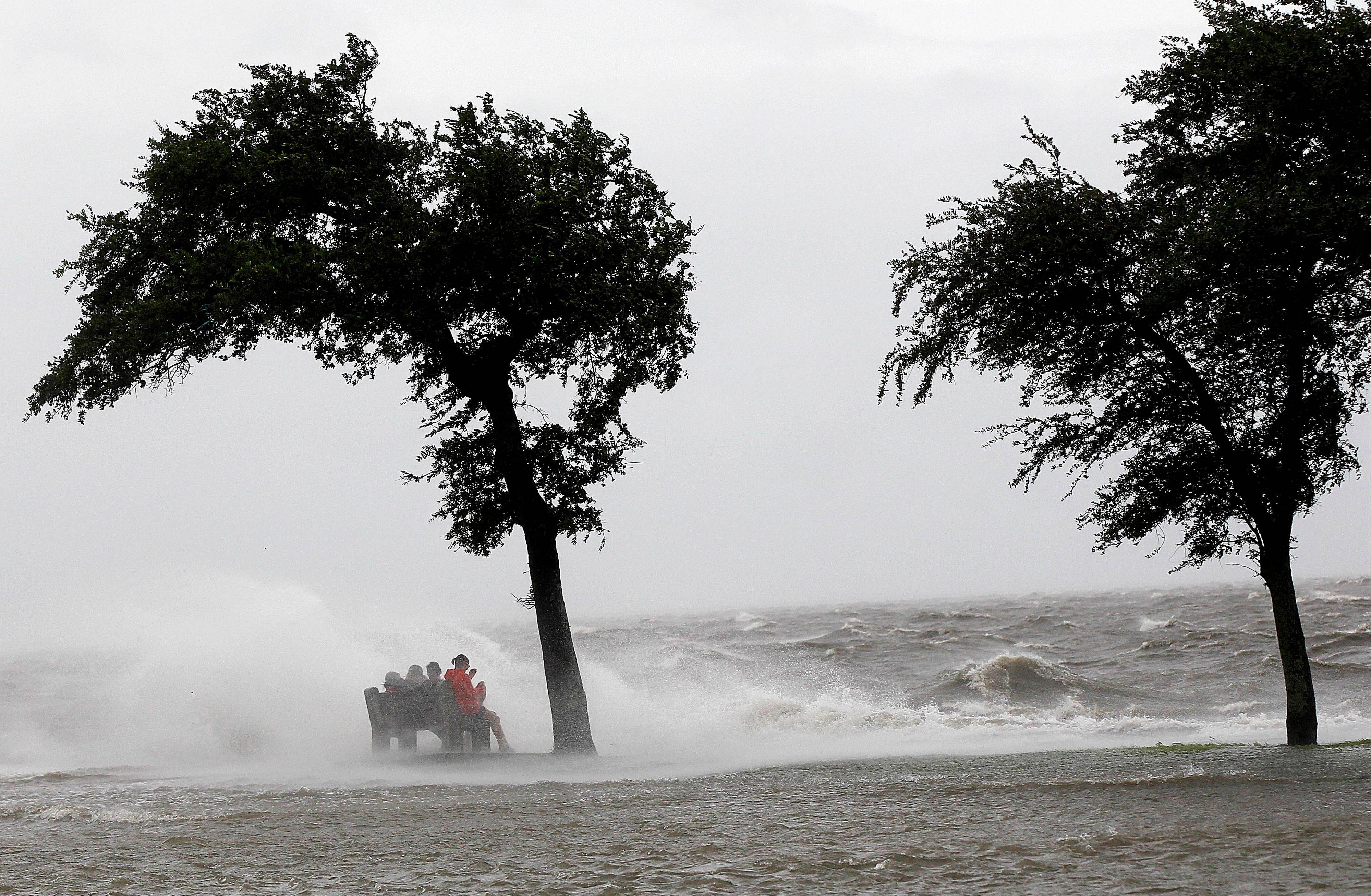 People sit on a bench along the seawall in the storm surge from Isaac, on Lakeshore Drive along Lake Pontchartrain, as the storm approaches landfall, in New Orleans, Tuesday, Aug. 28, 2012.