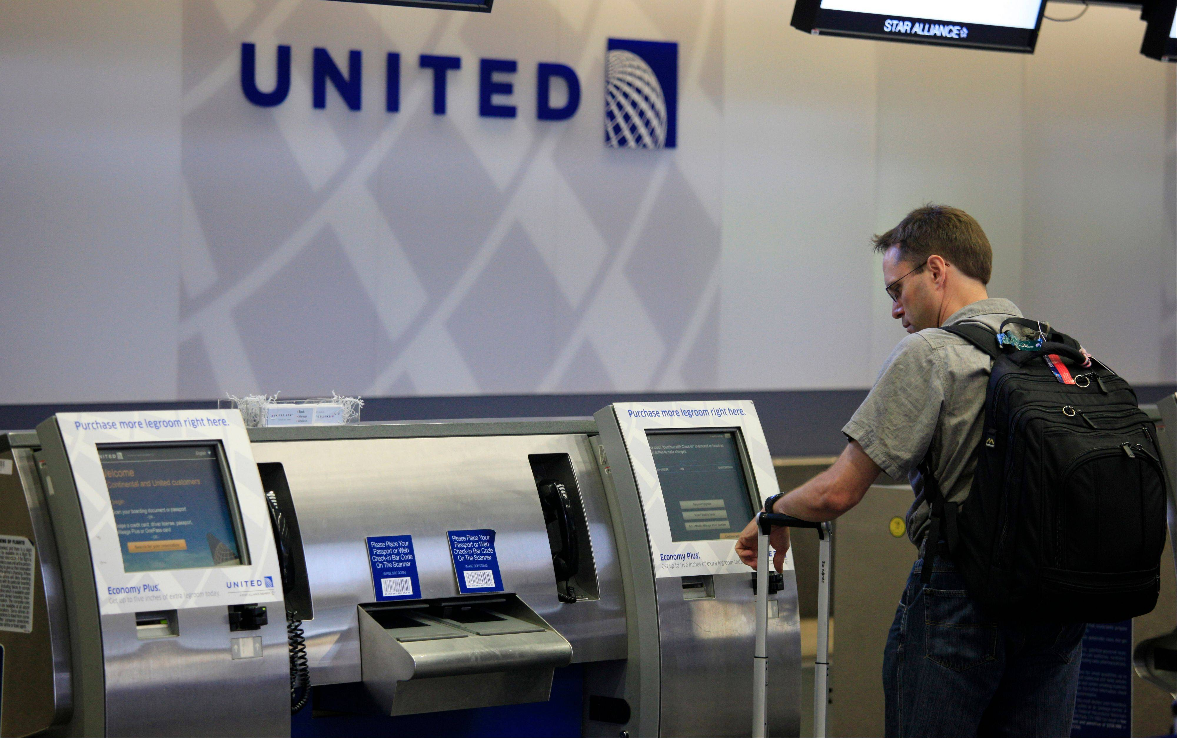 A man uses a United Airlines check-in kiosk at San Francisco last month. United passengers faced delays Tuesday after some of its major computer systems and website failed.