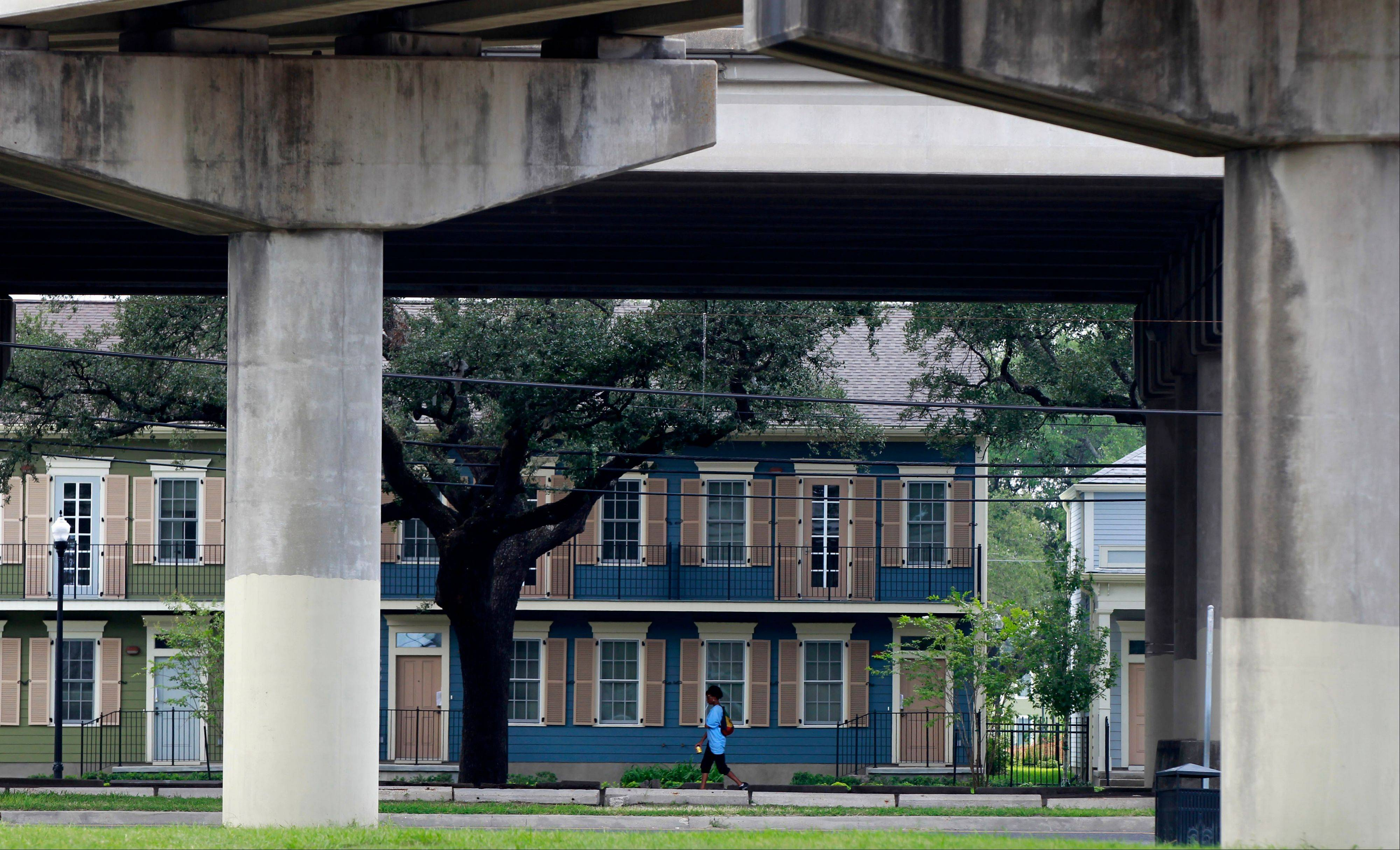 A woman walks past new public assisted housing where the Lafitte housing projects once stood, with the elevated Interstate 10 on Claiborne Ave. in the foreground in New Orleans.
