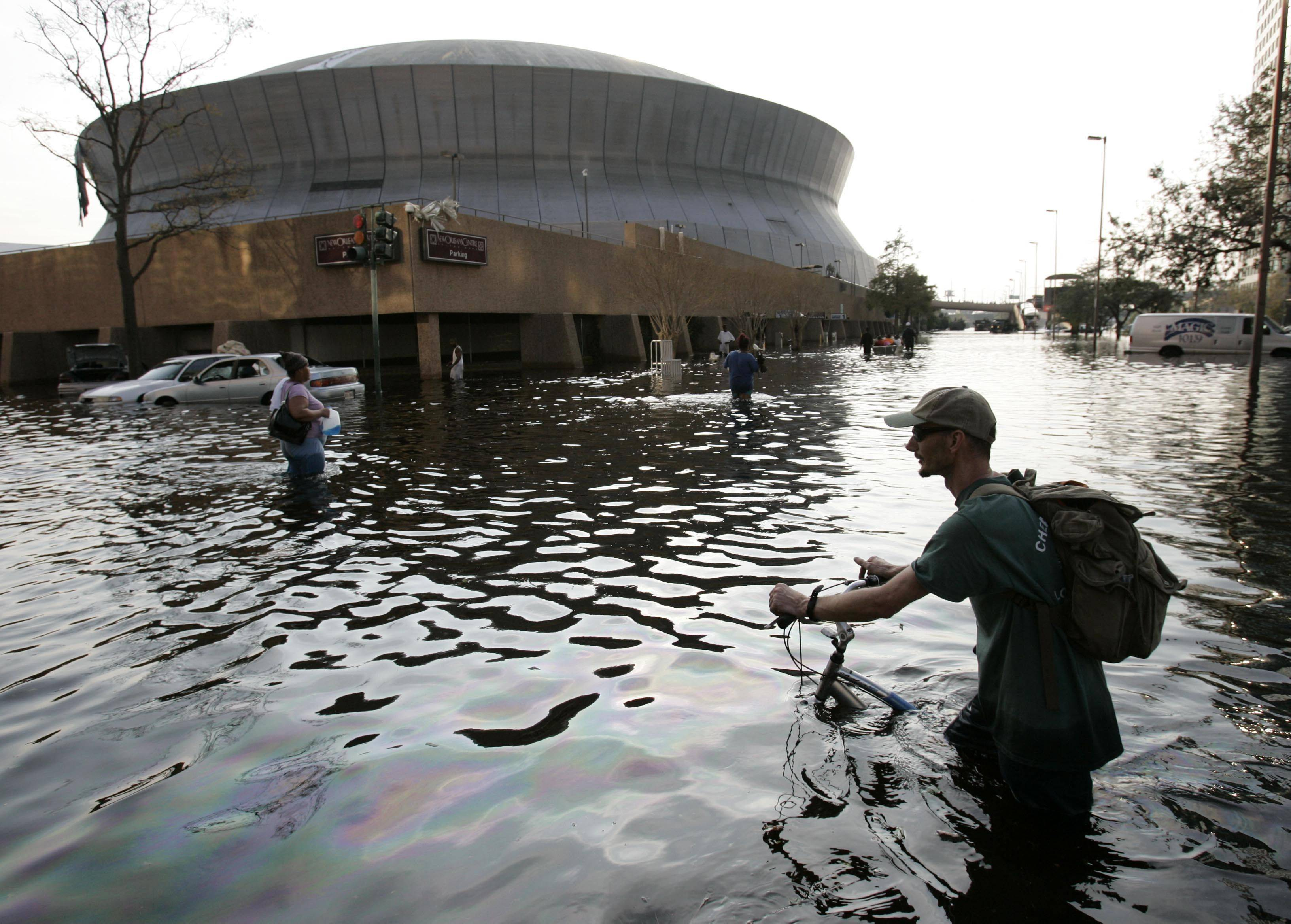 This Aug, 31, 2005 file photo shows a man pushing his bicycle through flood waters near the Superdome in New Orleans after Hurricane Katrina left much of the city under water.