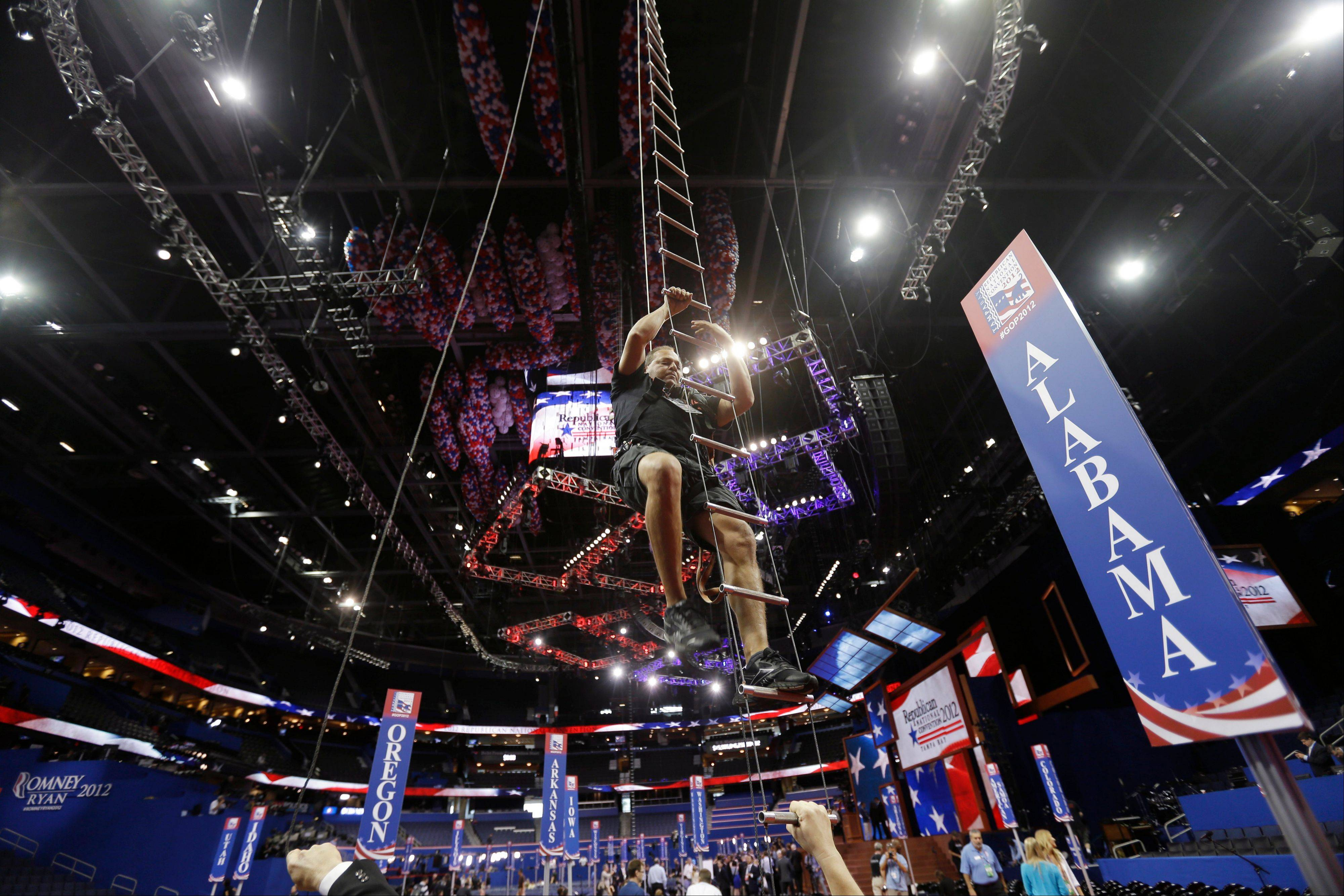 Rigger Omar Acebedo climbs down on on a ladder to floor of the Republican National Convention in the Tampa Bay Times