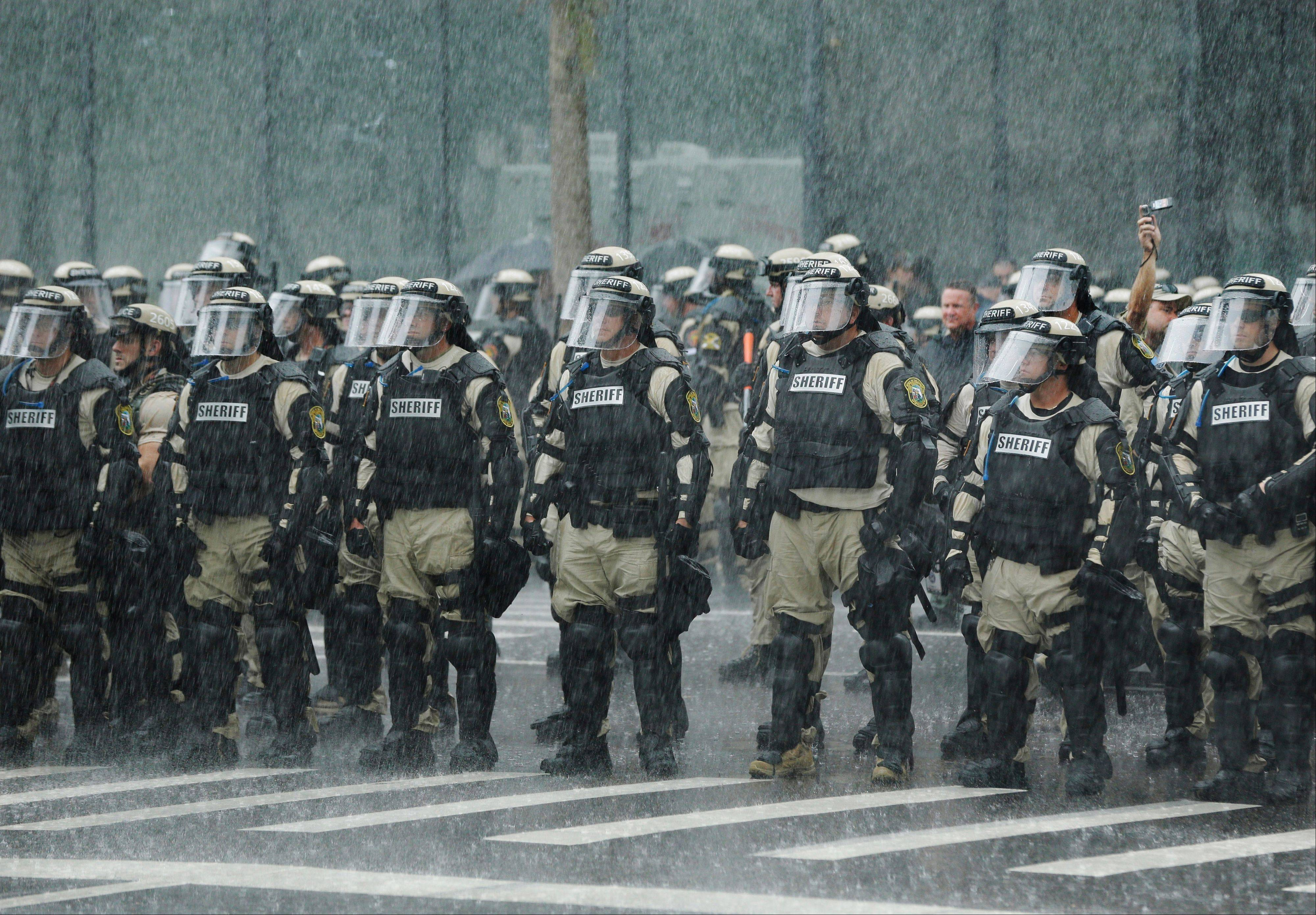 Police officers stand in a downpour as they watch demonstrators marching through the streets of Tampa, Fla., to protest the Republican National Convention Monday.
